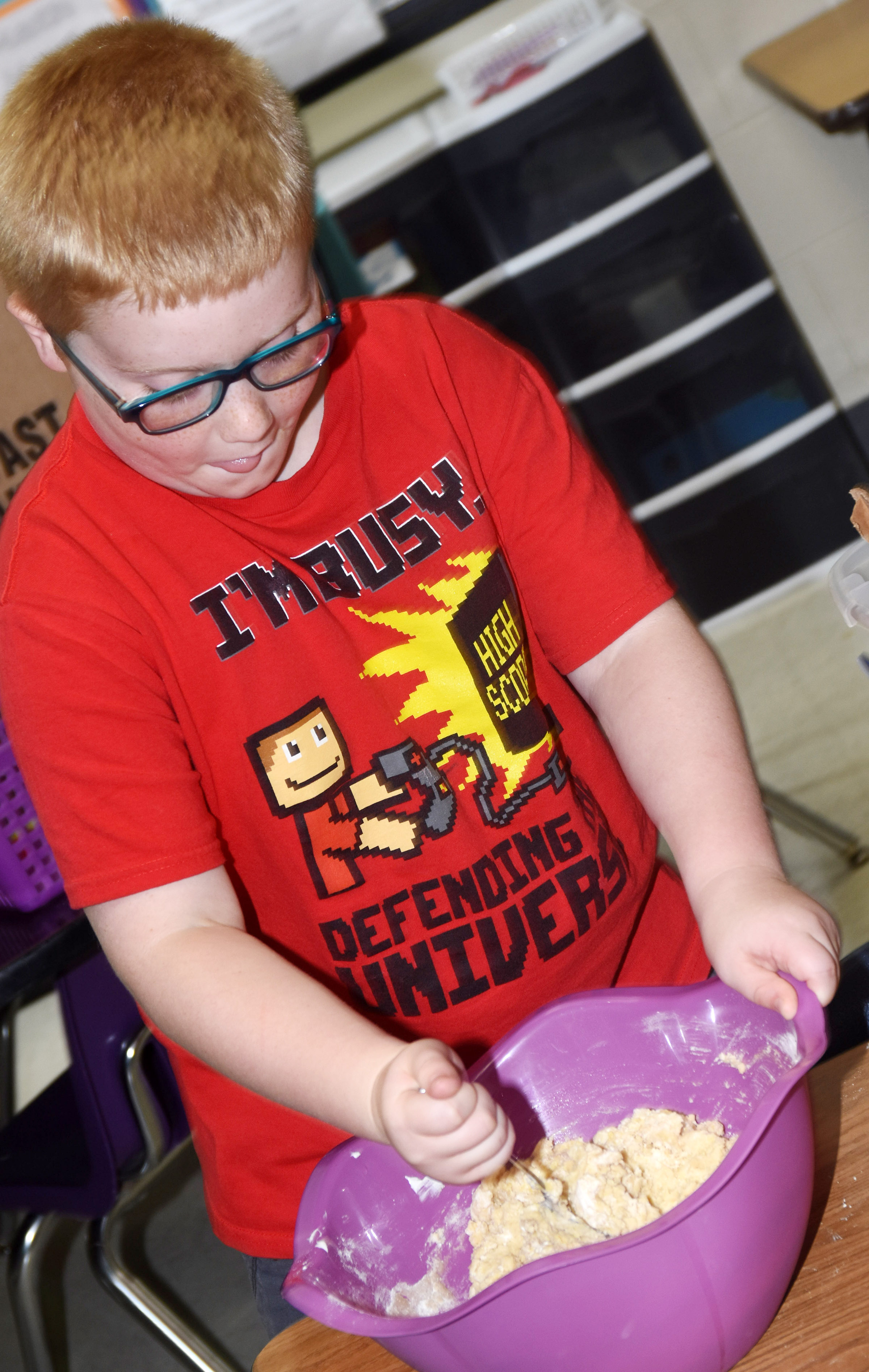 CES third-grader Aidan Bowles mixes ingredients to make homemade muffins.