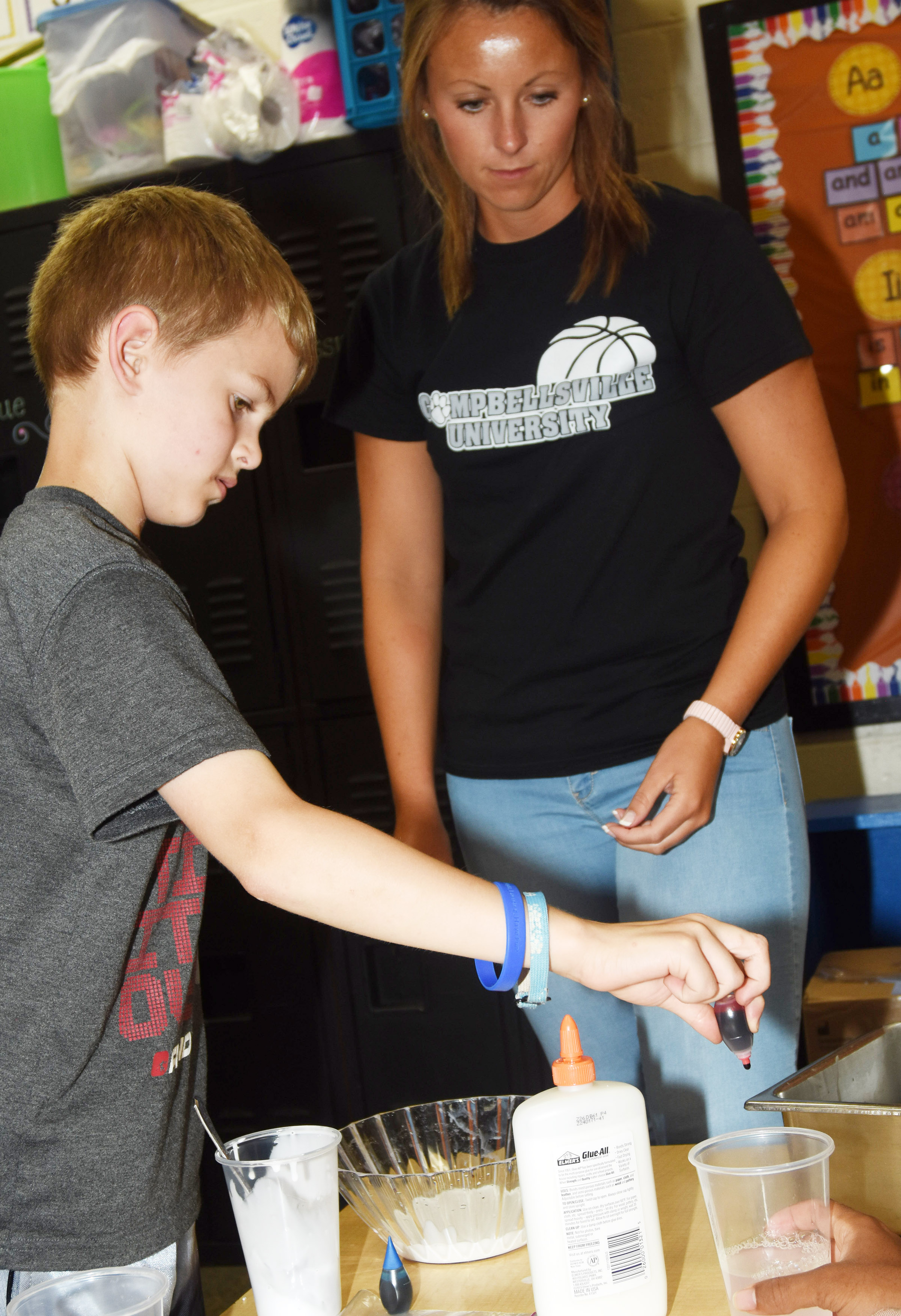 CES second-grader Logan Weddle adds food coloring to his class's slime, with help from teacher Kayla Bale.