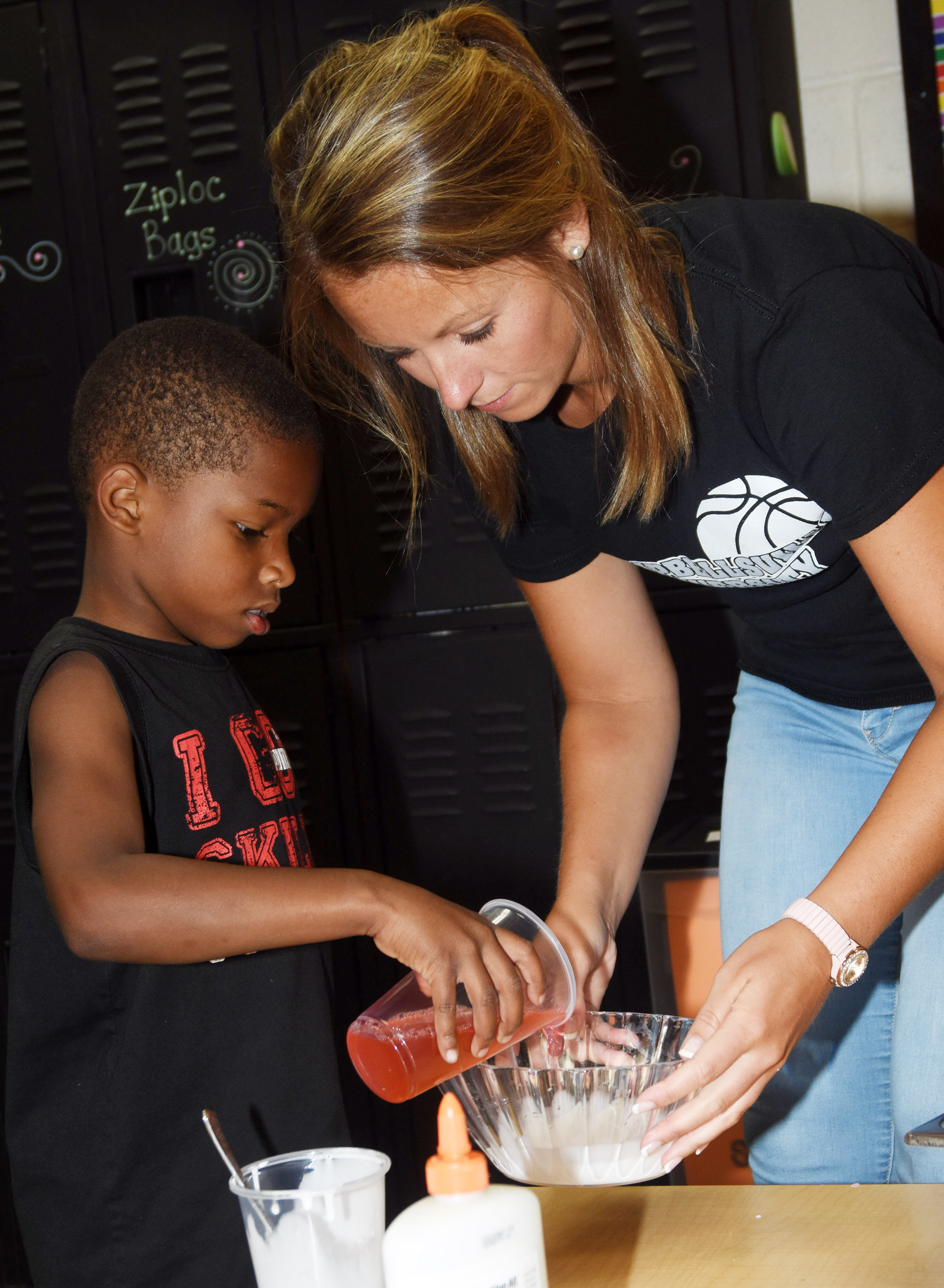 CES teacher Kayla Bale helps kindergartener Kaiyden Vancleave mix the ingredients to make slime.