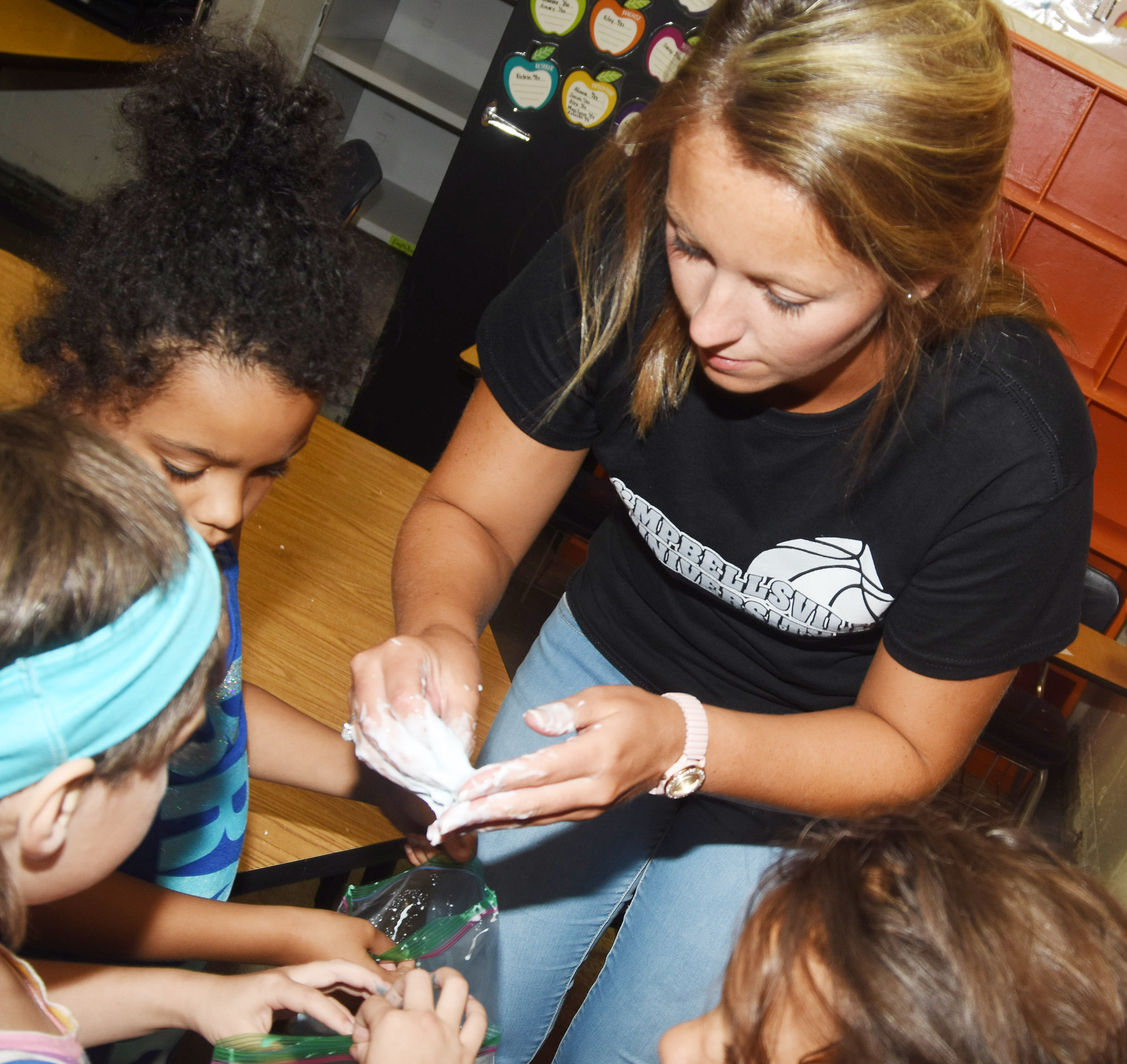 CES teacher Kayla Bale helps her students make slime.