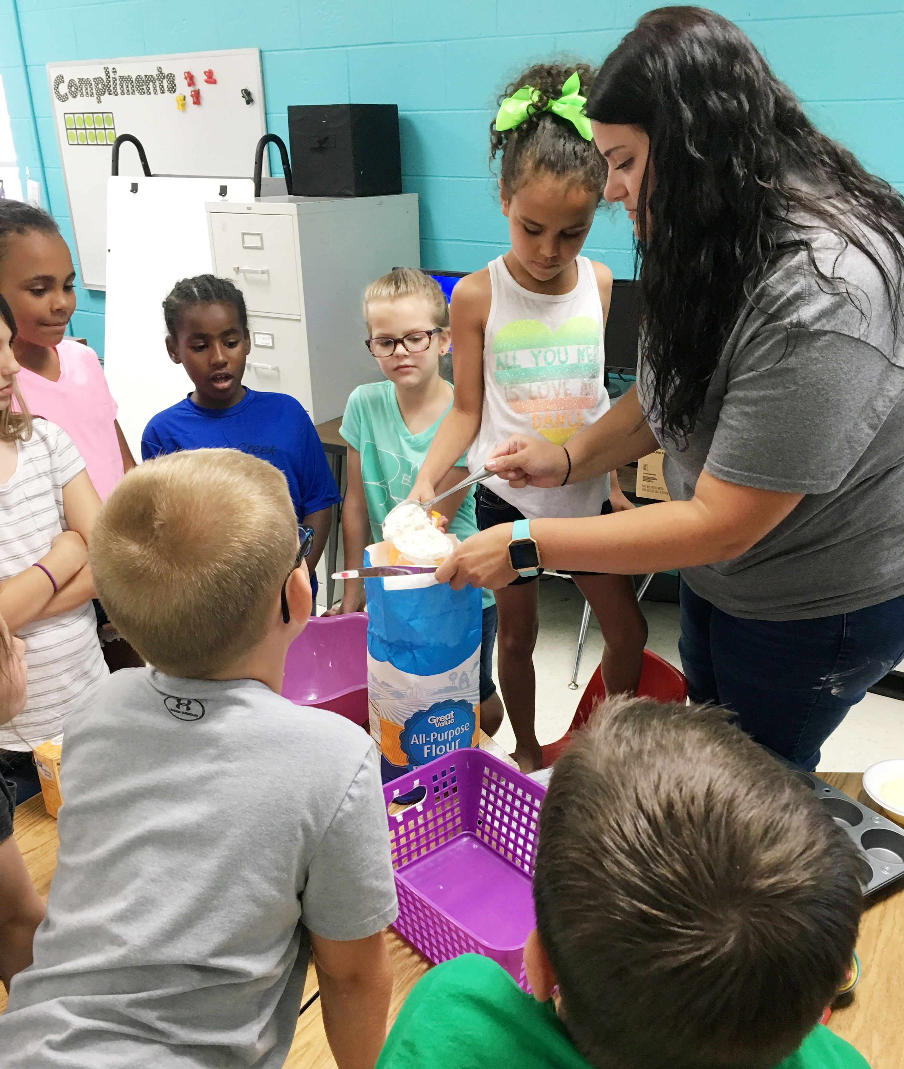 CES teacher Miriah Cox helps kindergartener Adelyn Litsey mix ingredients to make homemade muffins.