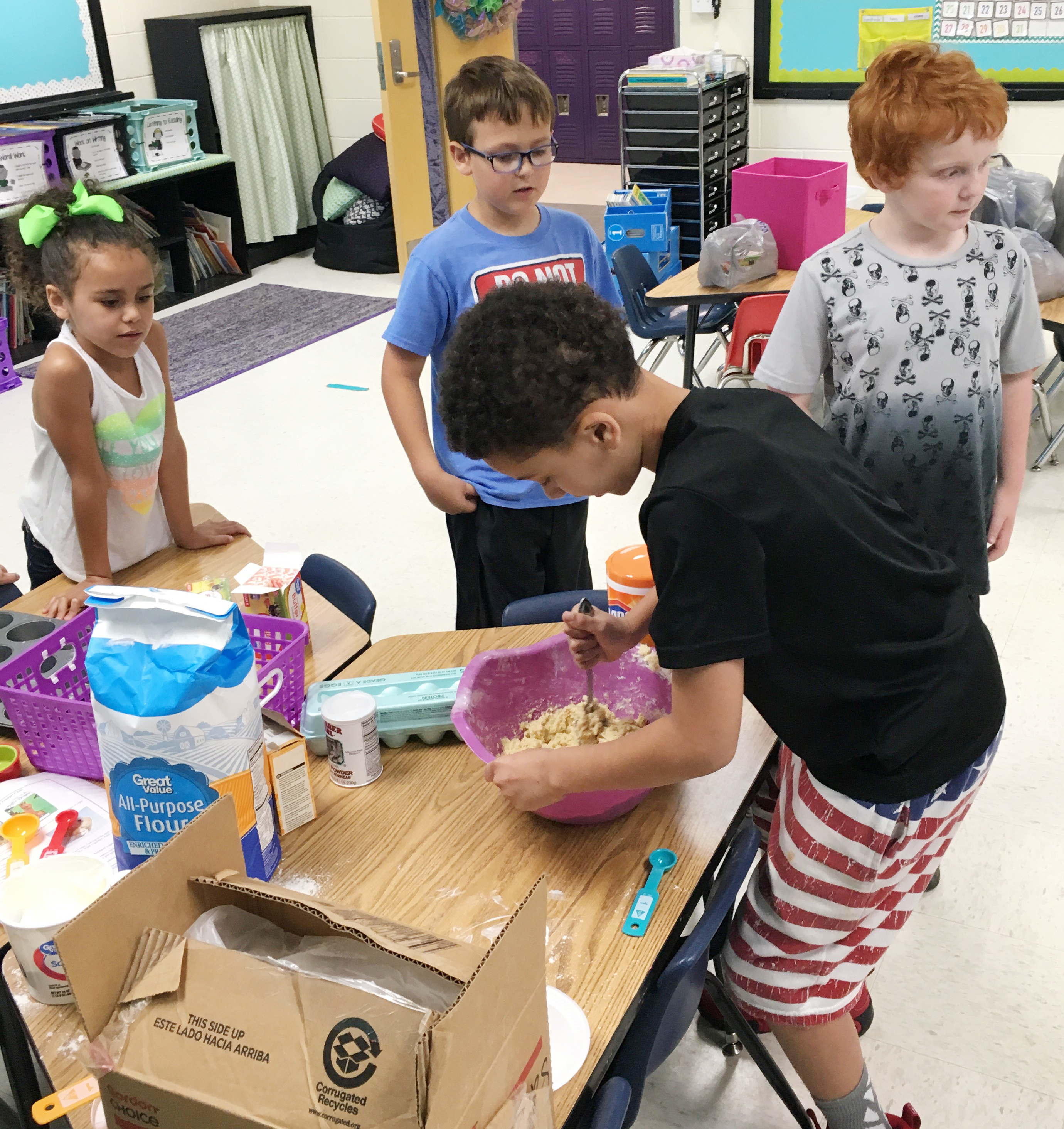 CES second-grader Bryant Mayo mixes ingredients to make homemade muffins.
