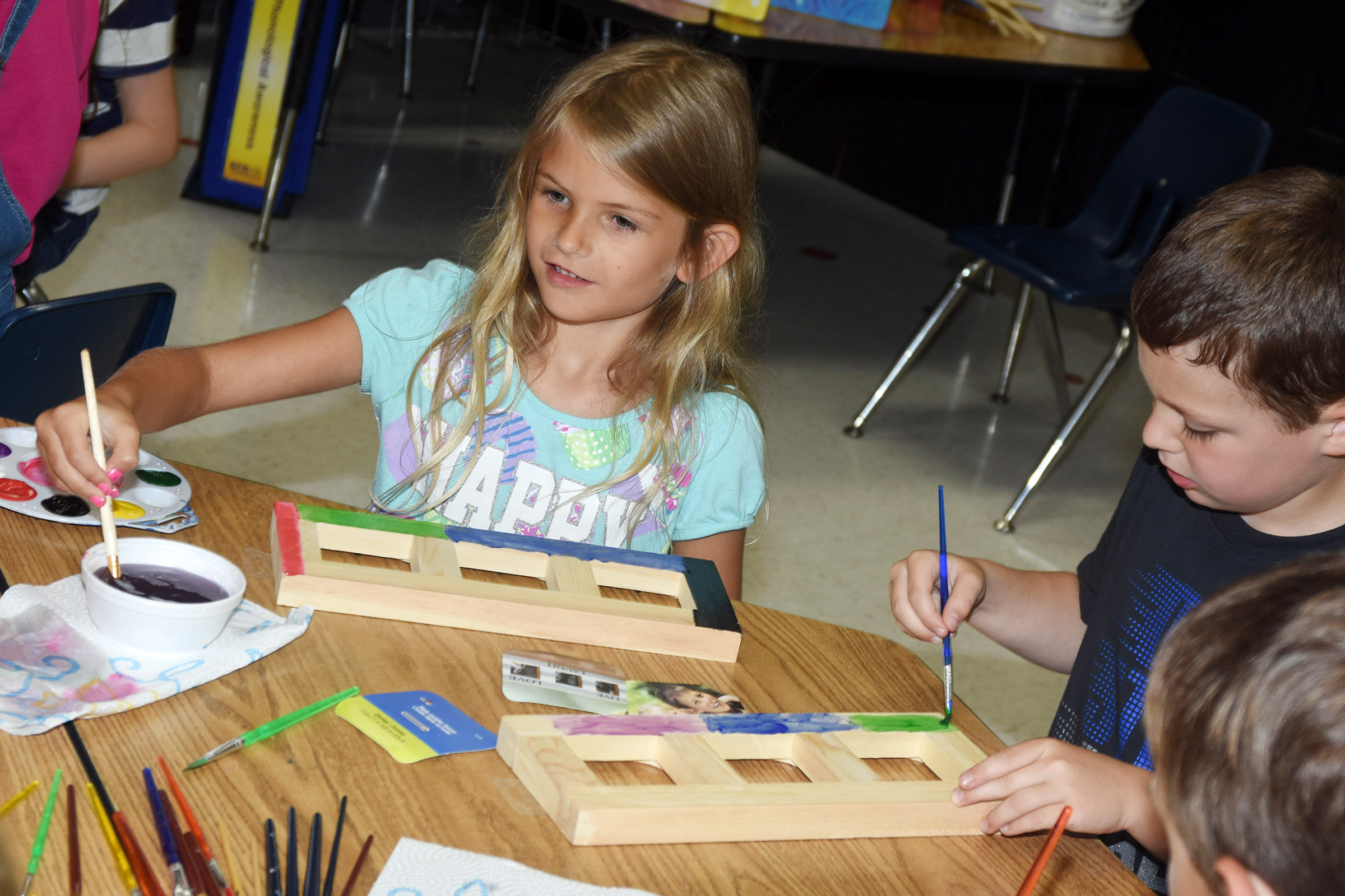 CES first-grader Gracie Gebler paints a picture frame with her classmates.