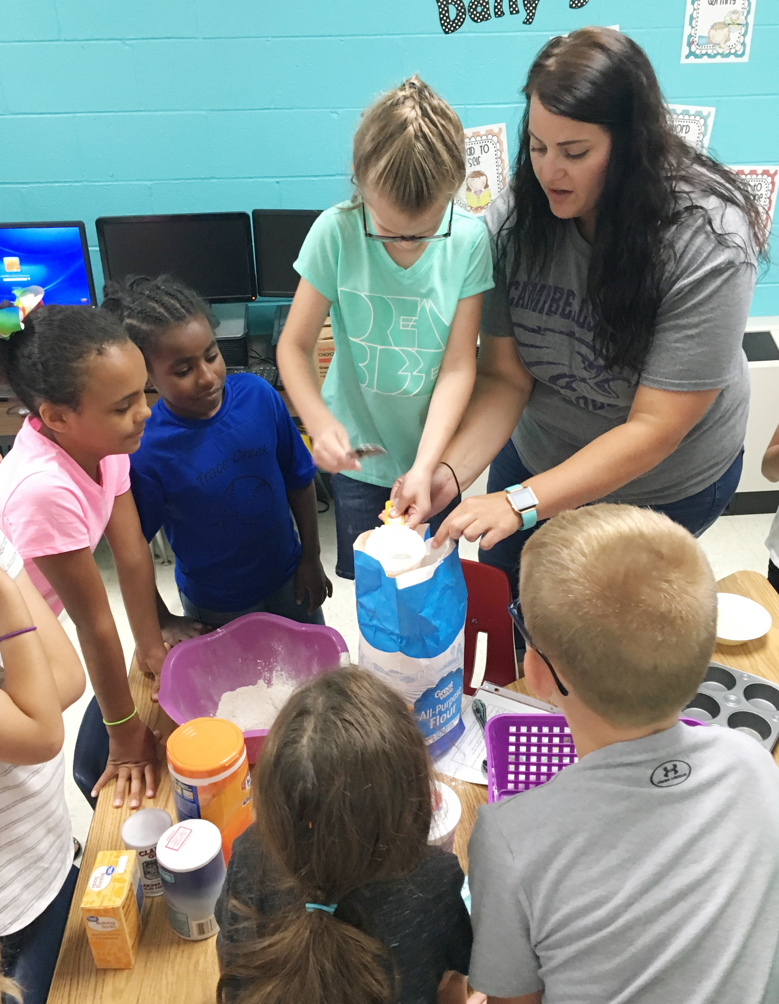 CES teacher Miriah Cox helps first-grader Zoe Weddle mix ingredients to make homemade muffins.
