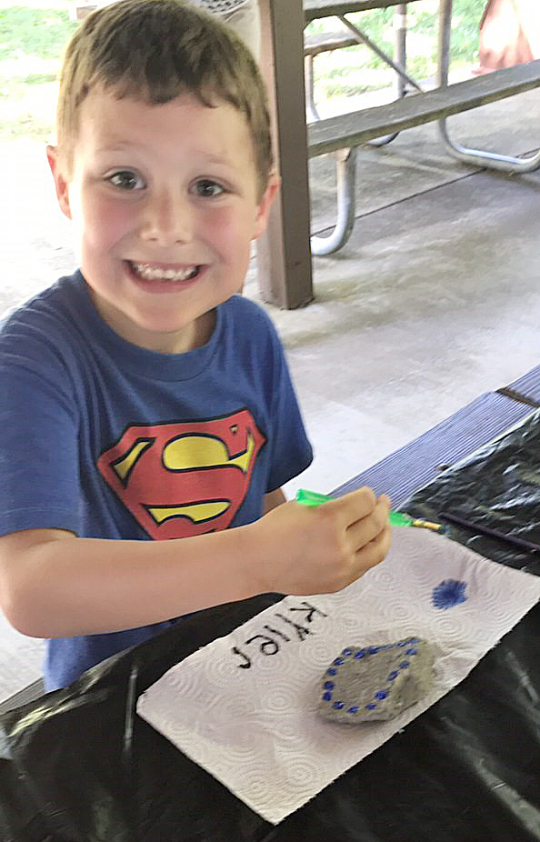 CES kindergartener Kyler Wilson paints a rock at Green River Lake.