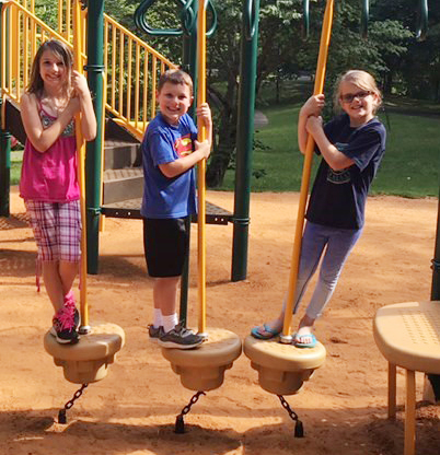 From left, CES third-grader Kairi Tucker, kindergartener Kyler Wilson and first-grader Zoe Weddle play on the playground at Green River Lake.