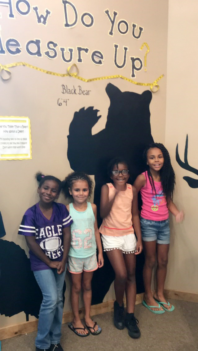 From left, CES second-grader Destini Gholston, kindergartener Adelyn Litsey, second-grader Willow Griffin and third-grader Braelyn Taylor pose for a photo to see how tall they are compared to a bear.