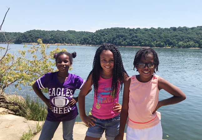 From left, CES second-grader Destini Gholston, third-grader Braelyn Taylor and second-grader Willow Griffin pose for a photo by Green River Lake.
