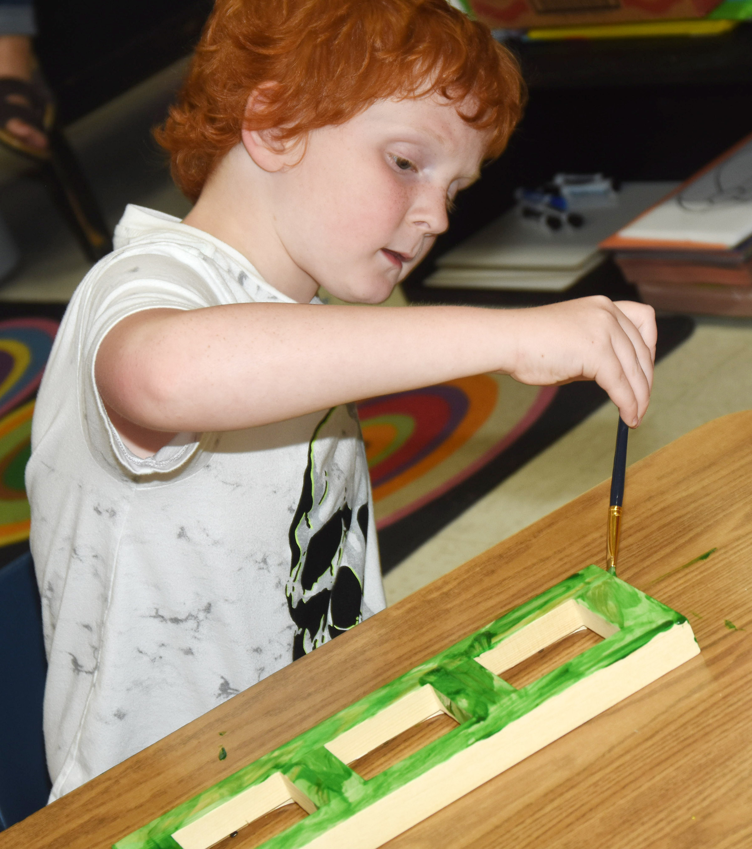 CES third-grader Gavin Martin paints a picture frame.