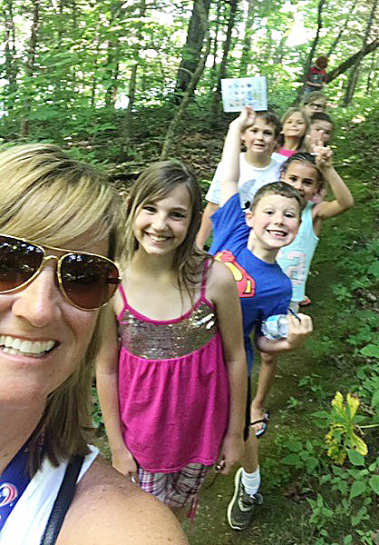 CES teacher Vanessa Adkins poses for a photo with her students as they go on a nature hike.