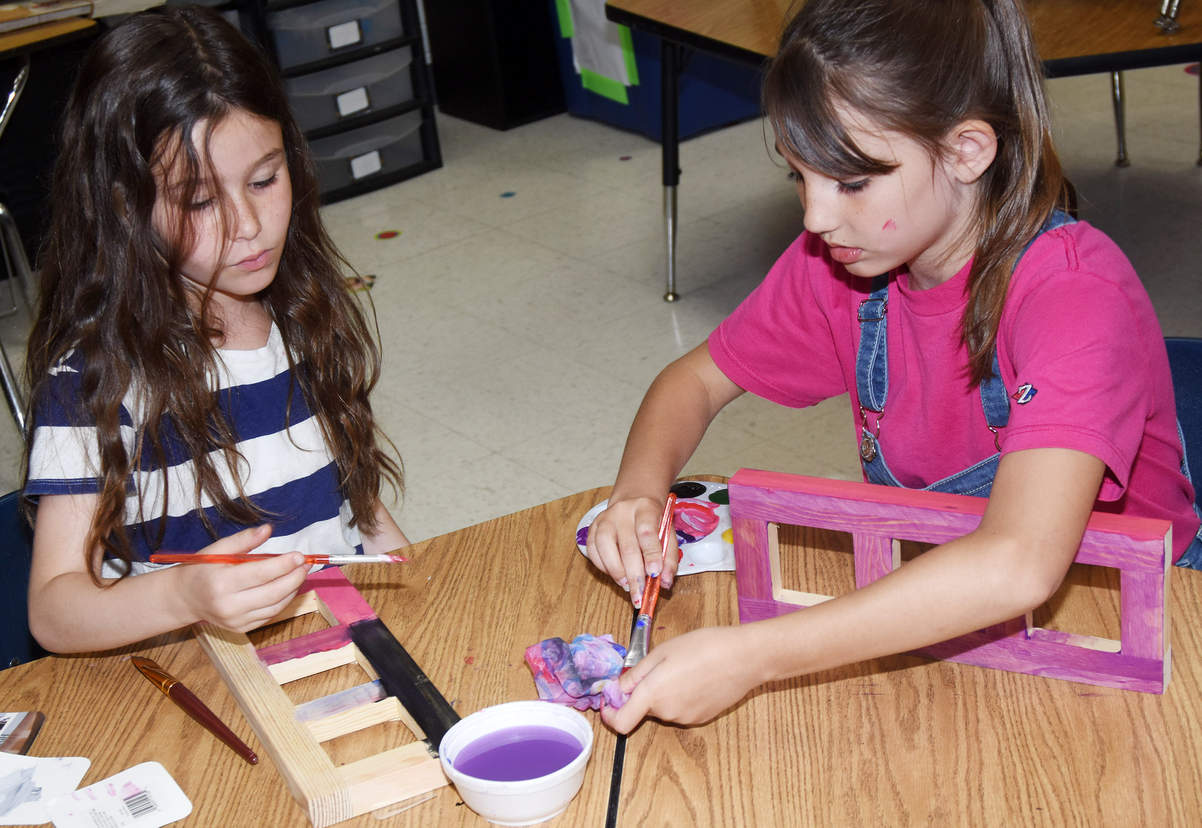 CES first-grader Stella Newcomb, at left, and third-grader Kairi Tucker paint picture frames.