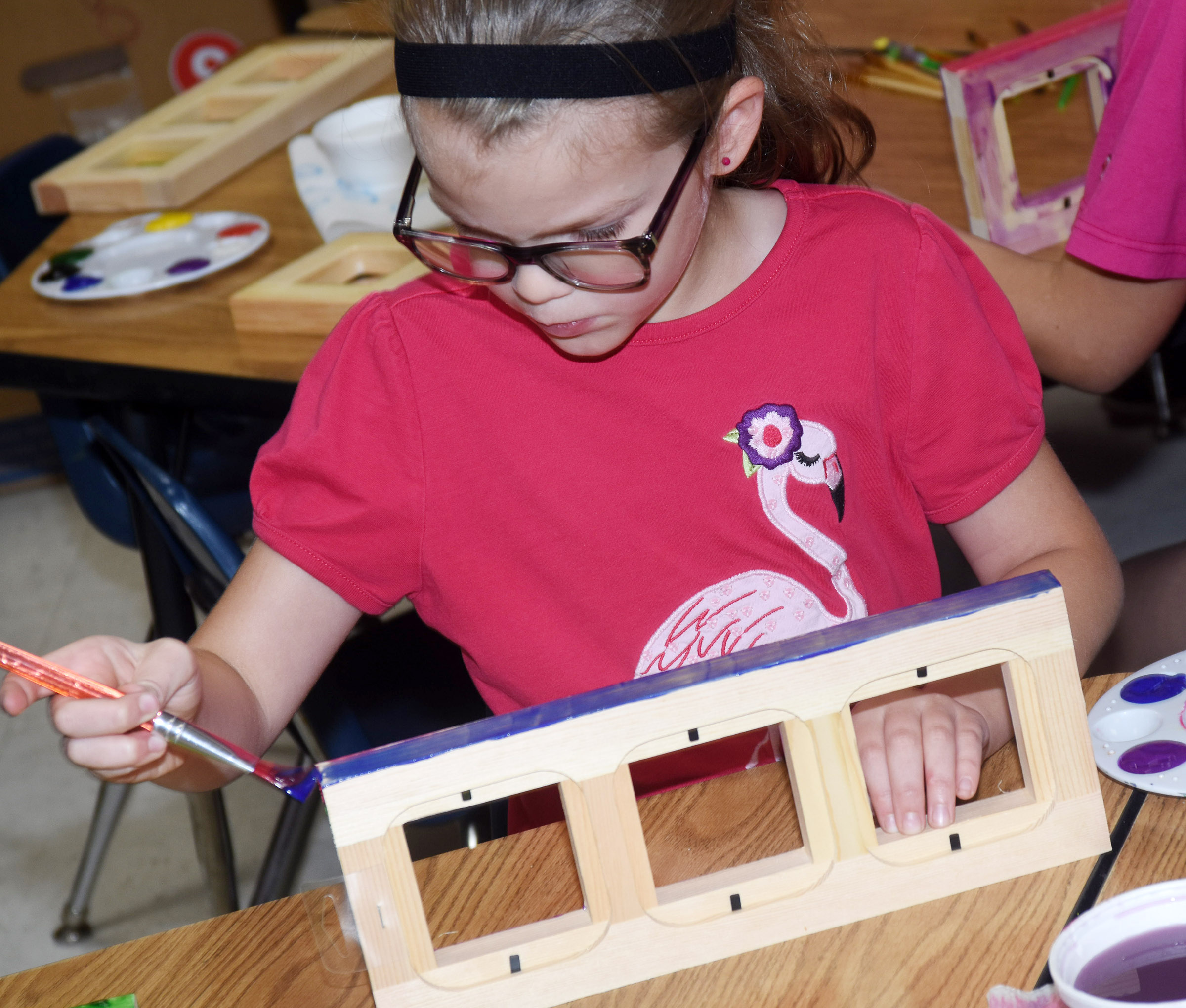 CES first-grader Zoe Weddle paints a picture frame.