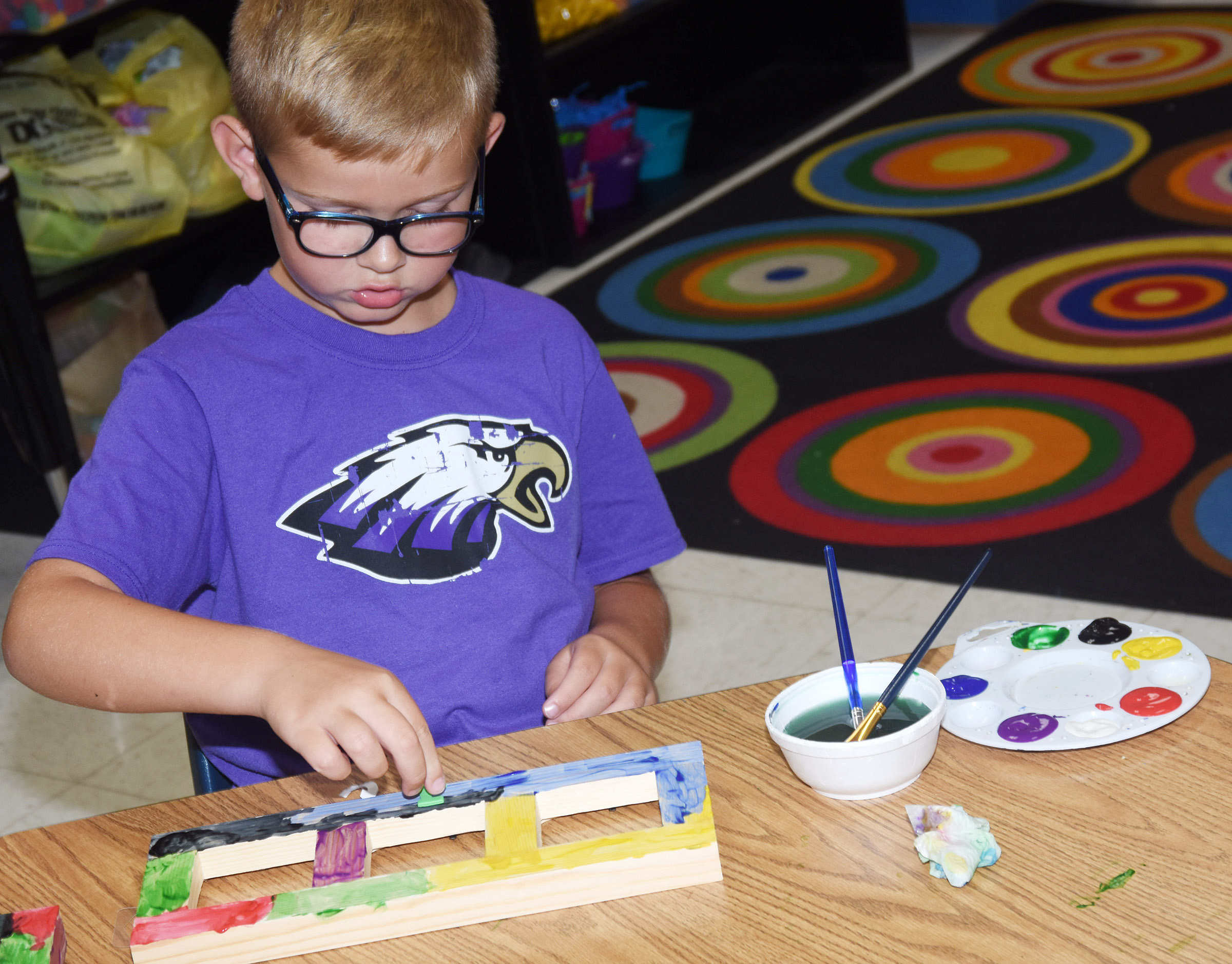 CES first-grader John Hagan Newton paints a picture frame.
