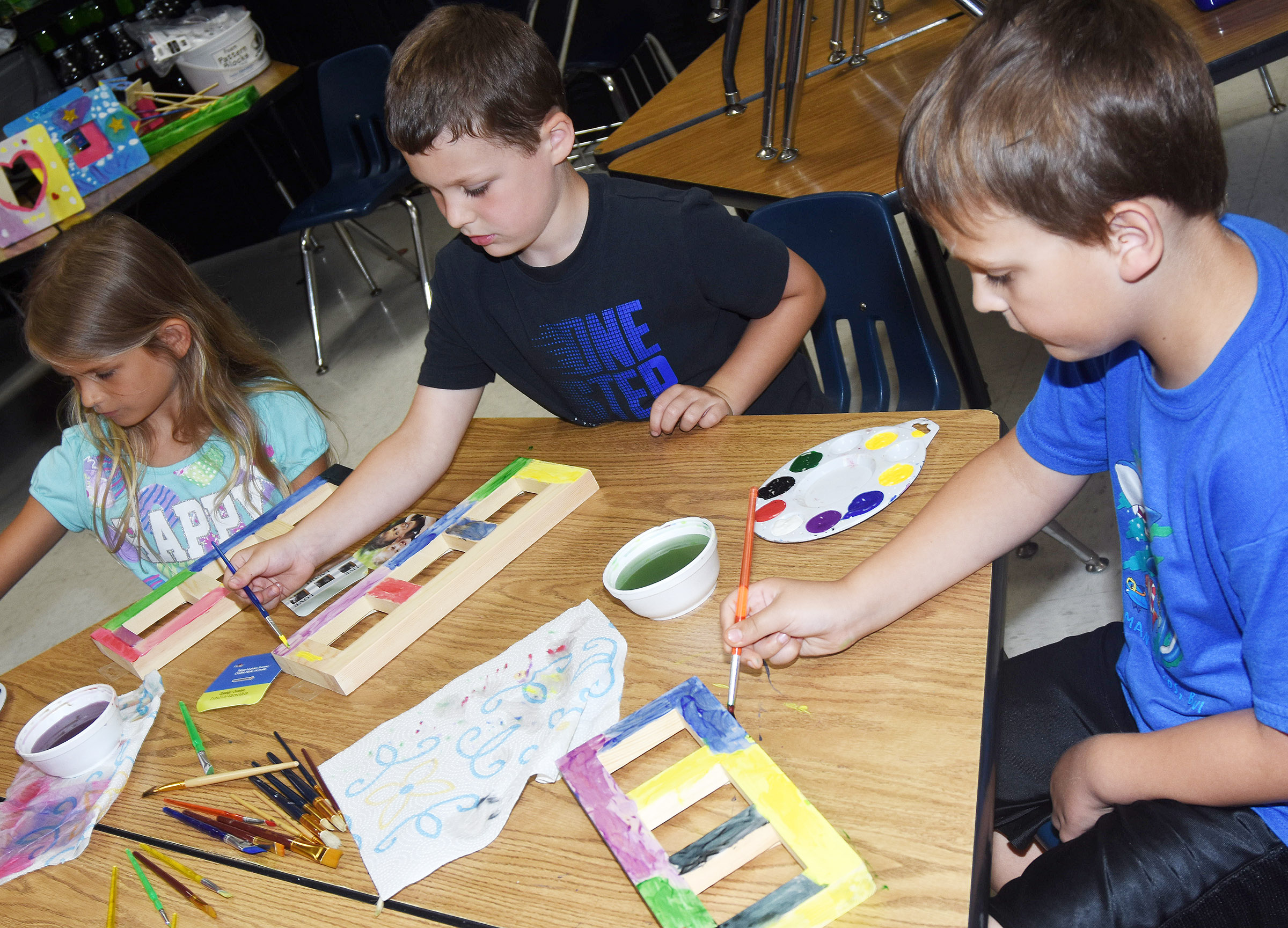 From left, CES first-grader Gracie Gebler, kindergartener Kyler Wilson and second-grader Brendan Martin paint picture frames.
