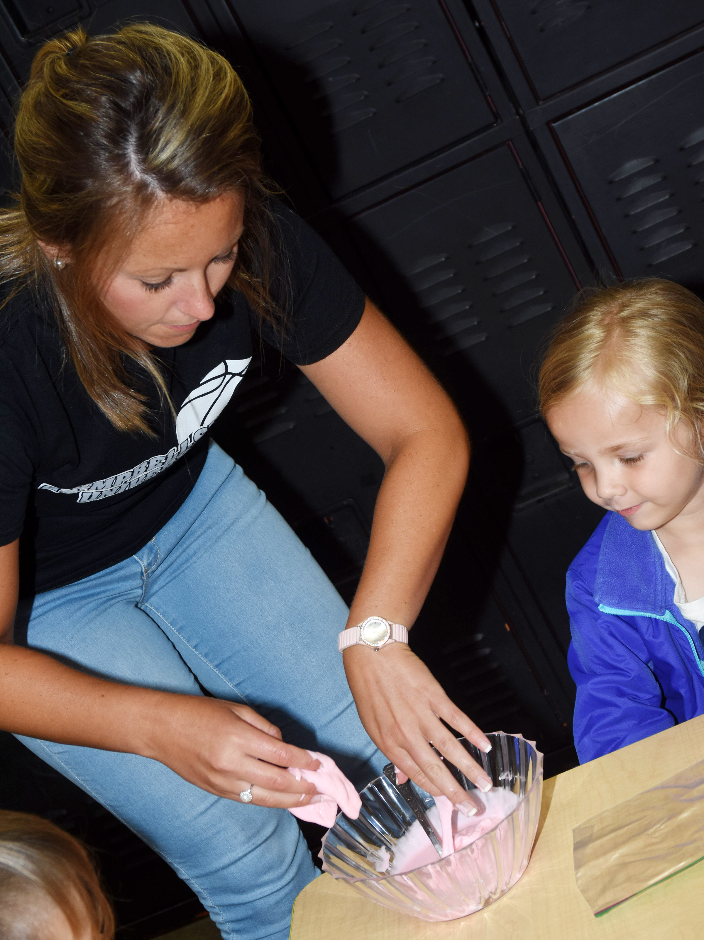CES teacher Kayla Bale helps kindergartener Trinidy Gribbins make slime.