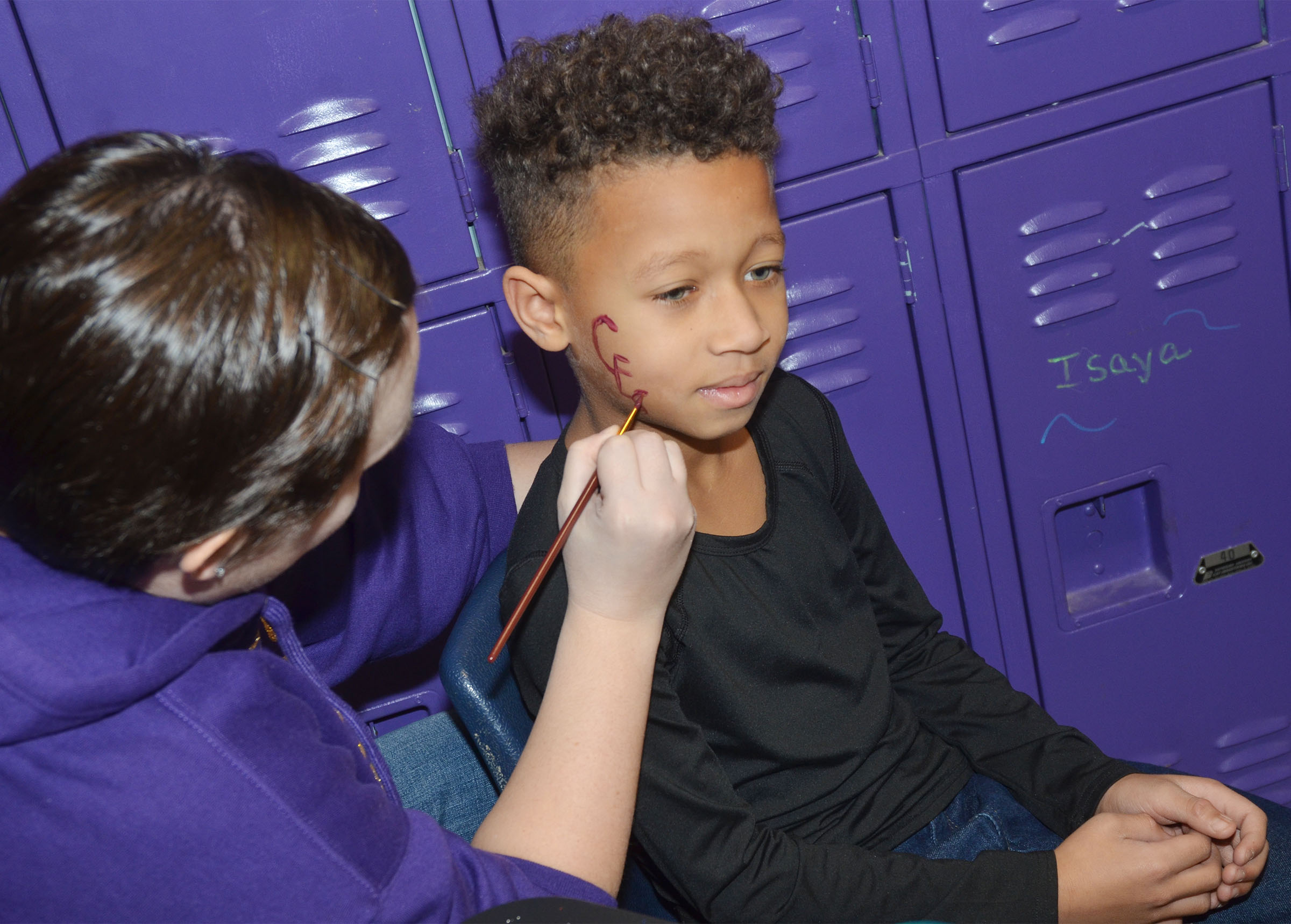 "CES second-grader Rajon Taylor has ""CES"" painted on his cheek by Wings Express Director Amanda Barnett."