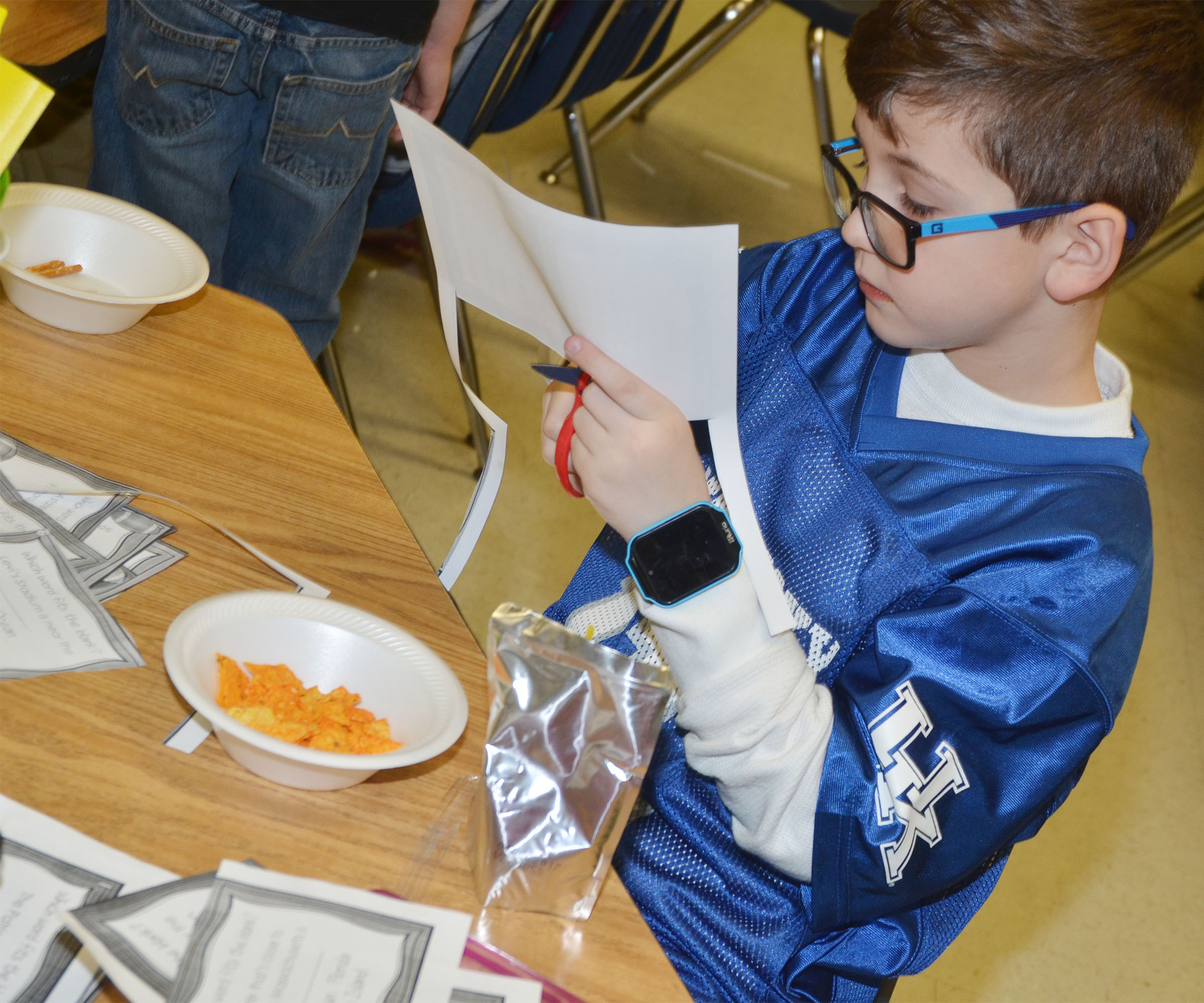 CES second-grader Rye Rhodes cuts out football trivia to make a booklet.