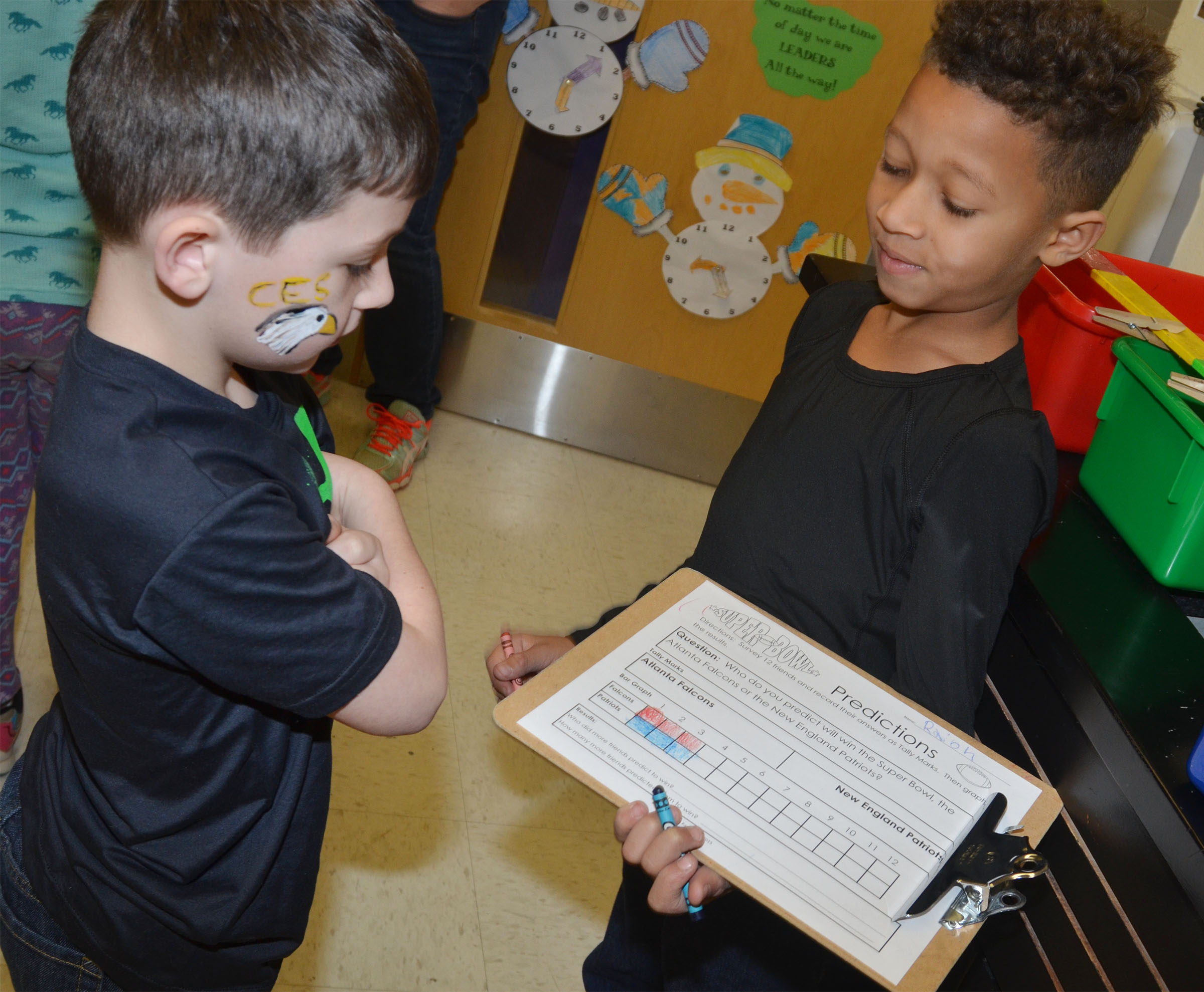 CES second-grader Rajon Taylor, at right, conducts a survey about which team his classmates believe will win the Super Bowl. At left is second-grader Codey Parks.