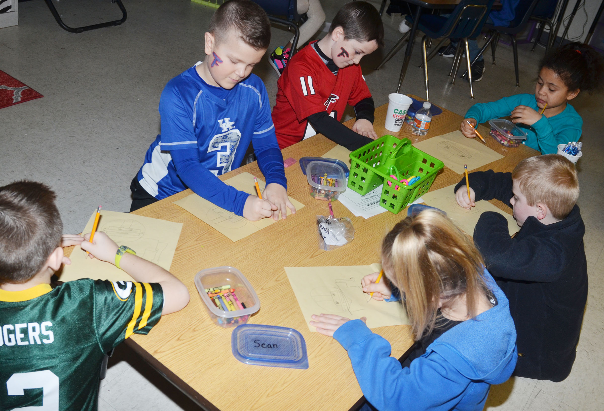 CES second-graders draw football players. Clockwise from left are Lanigan Price, Cayton Lawhorn, Luke Adkins, Alex Wilson, Aidan Bowles and Ava Ellis.