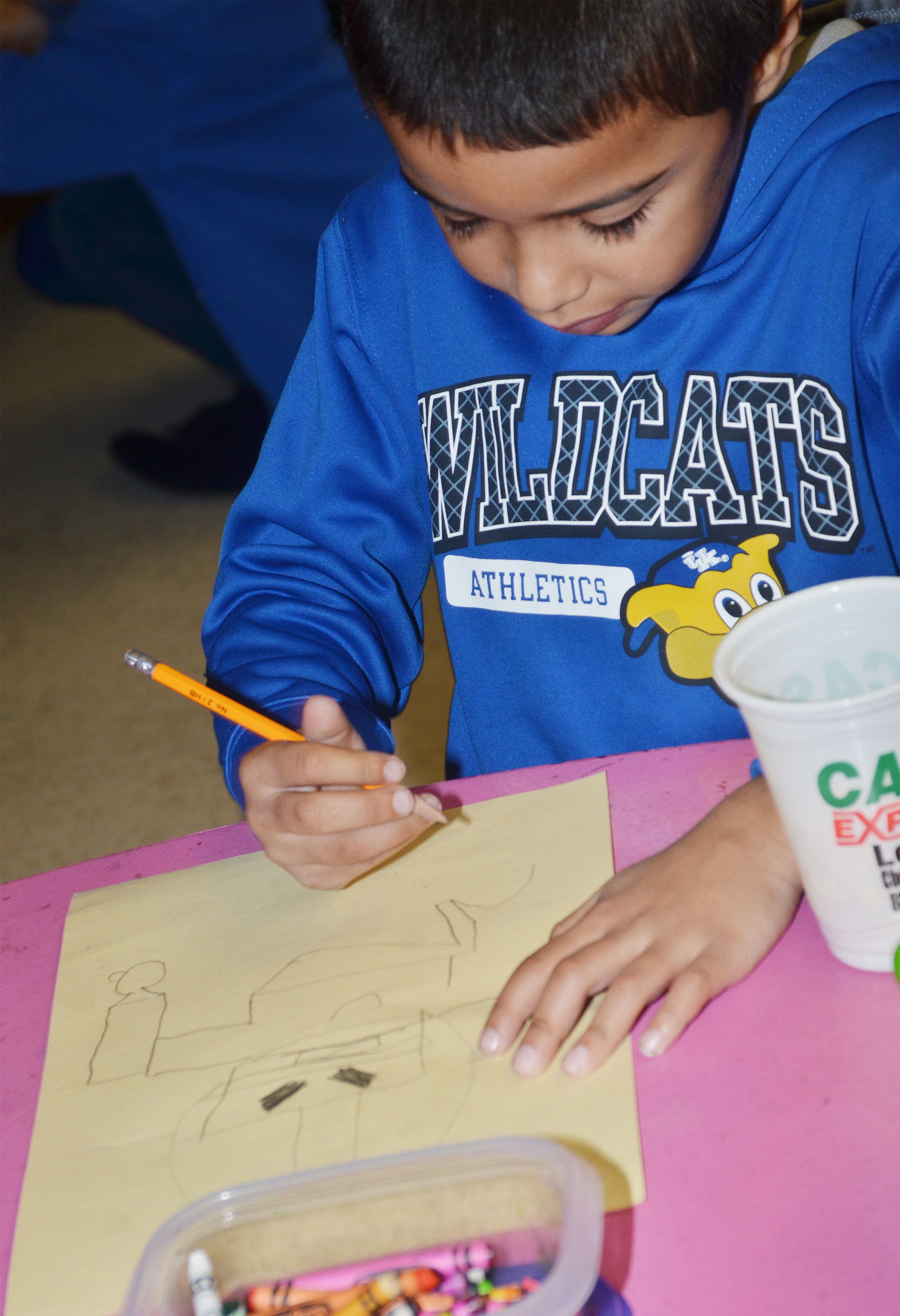 CES second-grader Keylan Strong draws a football player.