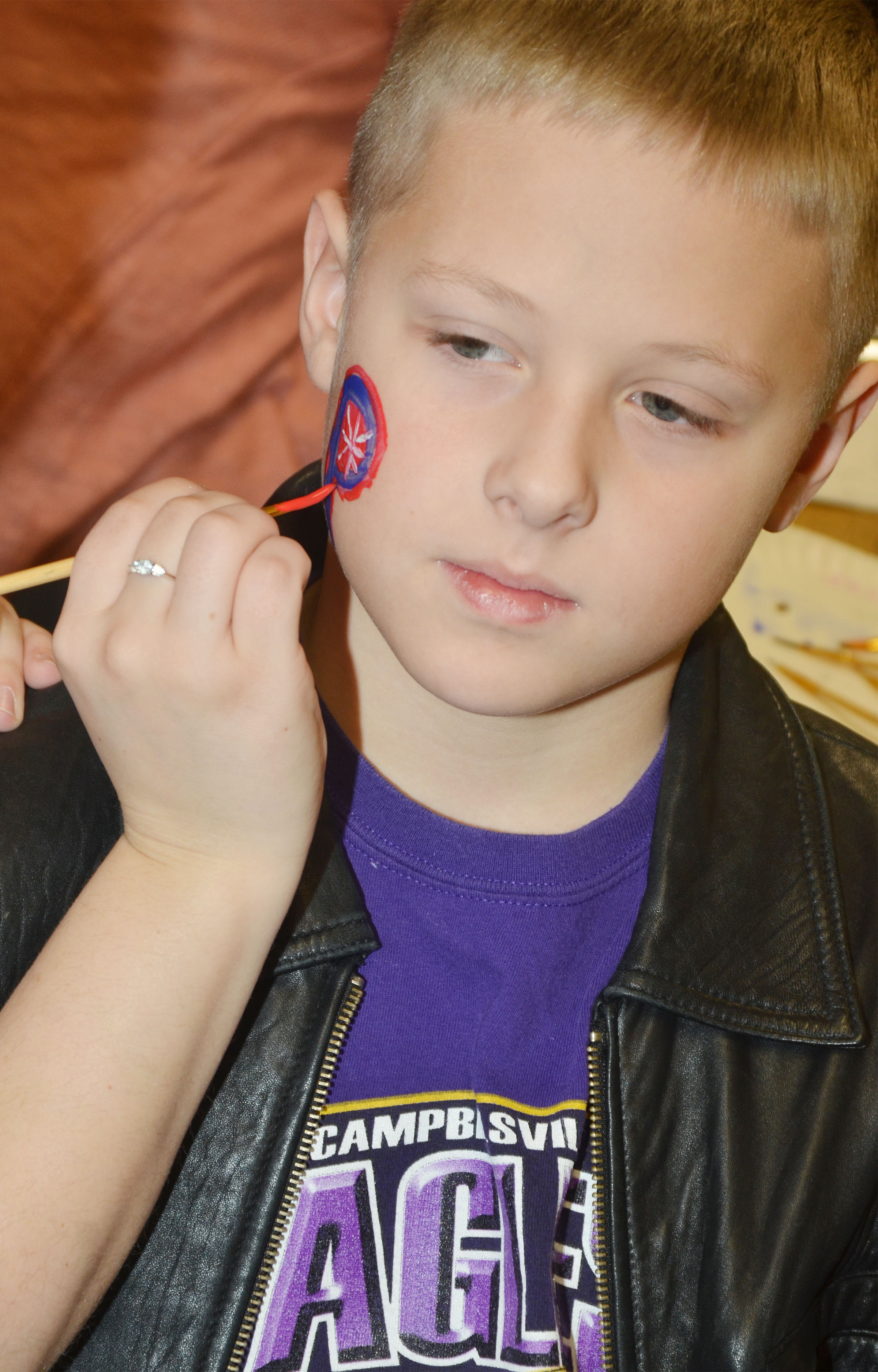 CES second-grader Evan Lockridge gets a New England Patriots logo painted on his cheek.