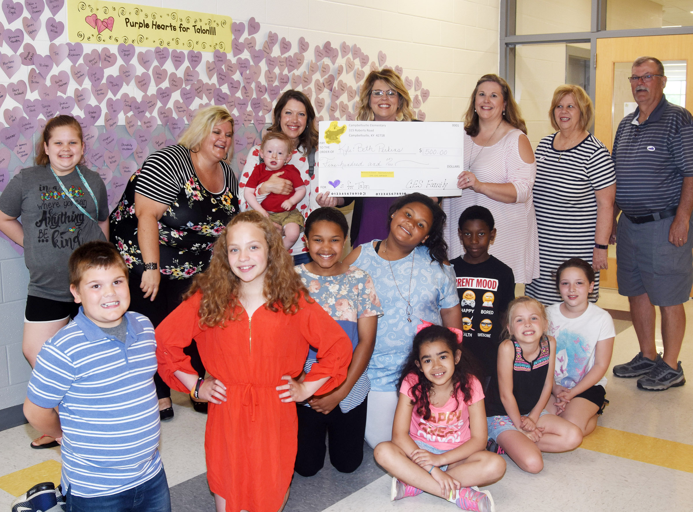 Campbellsville Elementary School students and staff members recently raised $500 to help Talon Perkins, 1, who was born with a congenital heart disease and pulmonary vein stenosis. Students recently presented Talon and his family members with a check. CES students in front are, from left, fifth-graders Logan England, Deanna Reardon, Jaclyn Jackson and Dezarae Washington and third-graders Sophia Santos, Jaron Johnson, Ava Ellis and Keely Rakes. Back, Talon's cousin Kyndall Cox, Talon's aunt Allison, Cox, an exceptional child educator at CES, Beth Perkins holding Talon, CES Principal Elisha Rhodes, CES music teacher Cyndi Chadwick and Talon's grandparents Cindy and Tommy Perkins.