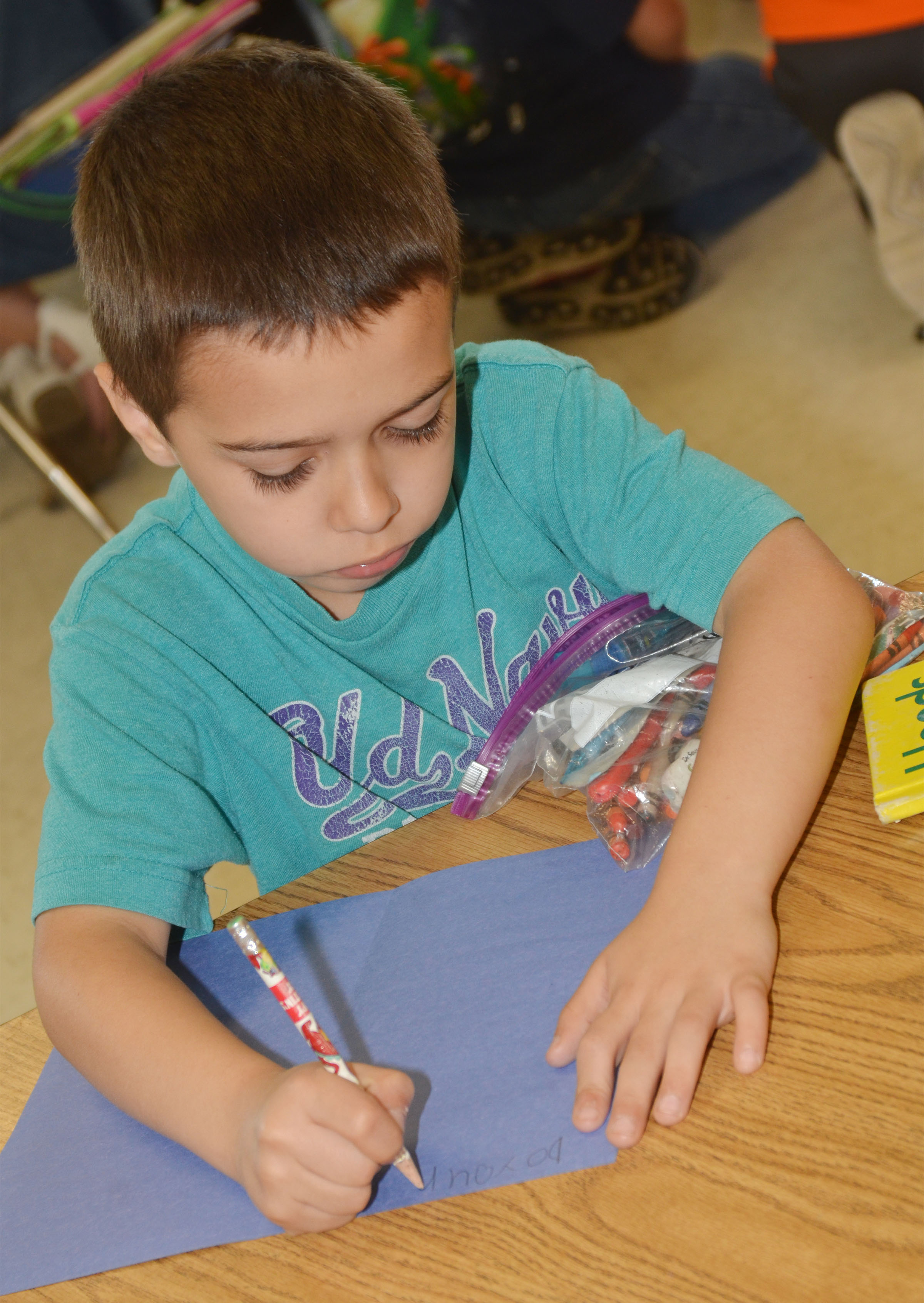 CES first-grader Brenden Chastain makes a card for a third-grade student.