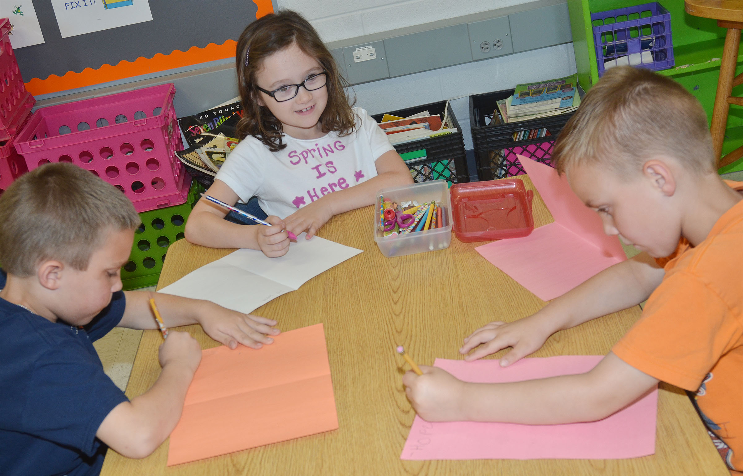 From left, CES first-graders Nikolas Torres, Anna Keith and Hunter Bates make cards for third-grade students.