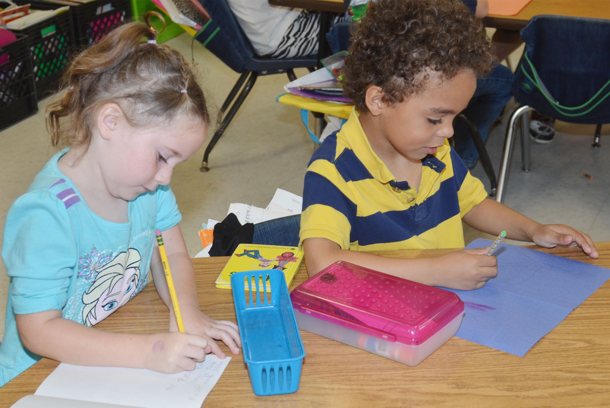 CES first-graders Kinsley Graham, at left, and Javion Milby make cards for third-grade students.