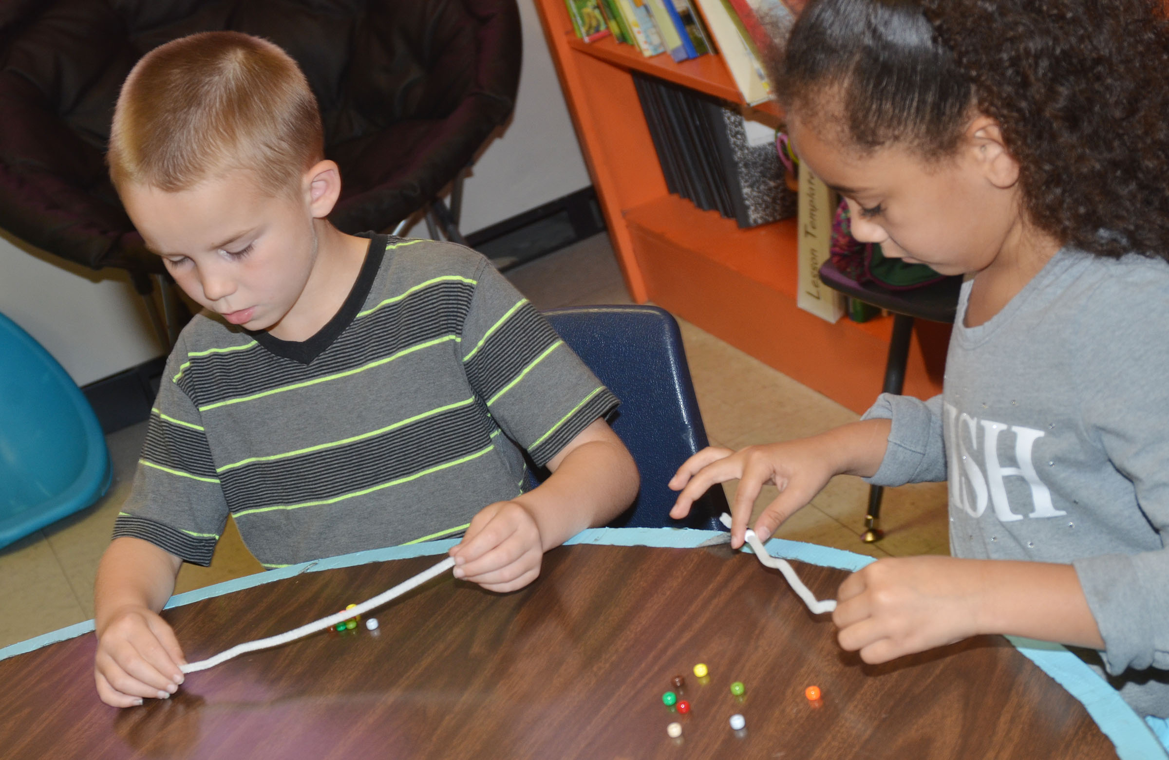 CES first-graders Jackson Bates, at left, and Keitona Whitehead make their Thanksgiving bracelets.