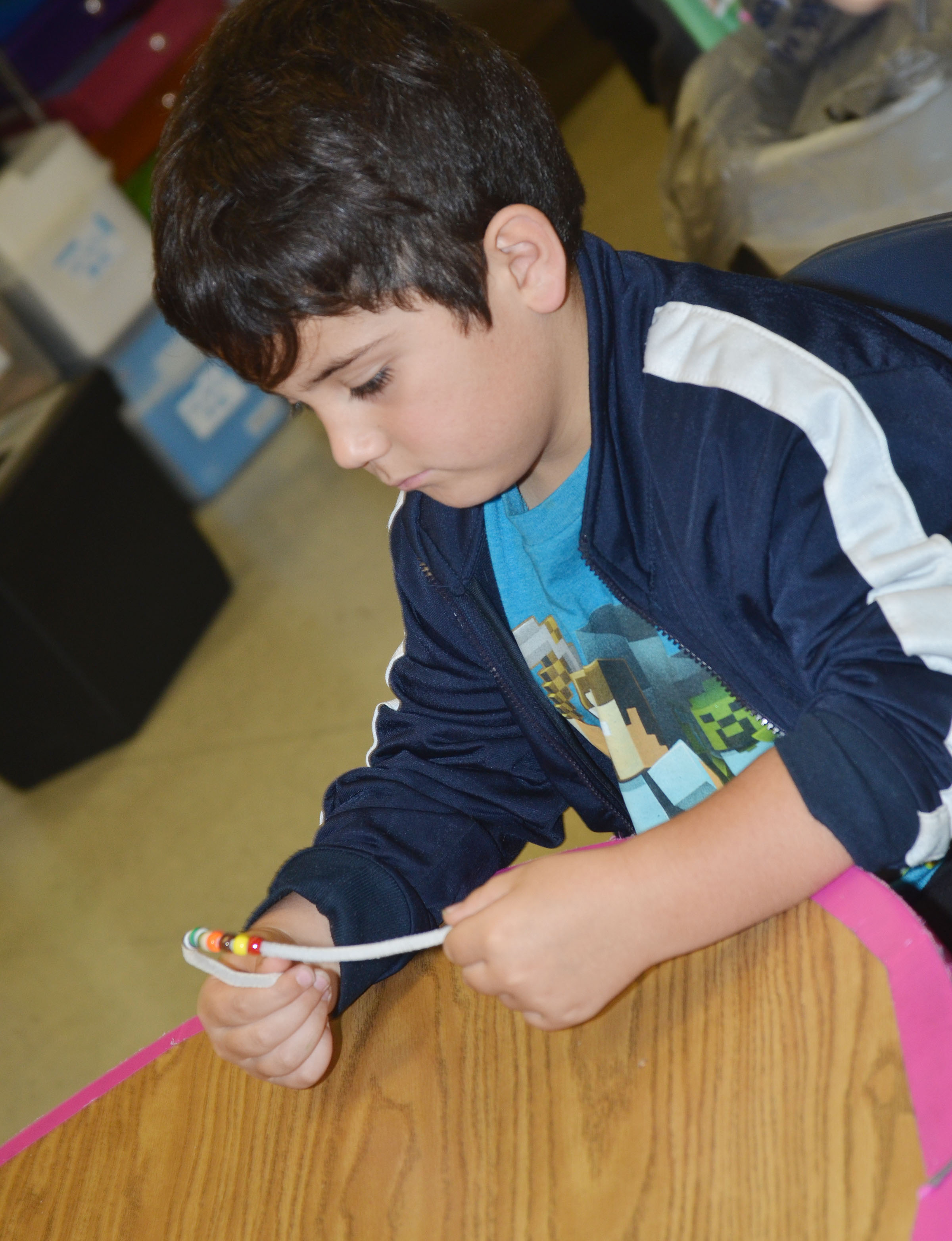 CES first-grader Nicholas Almeida makes his Thanksgiving bracelet.