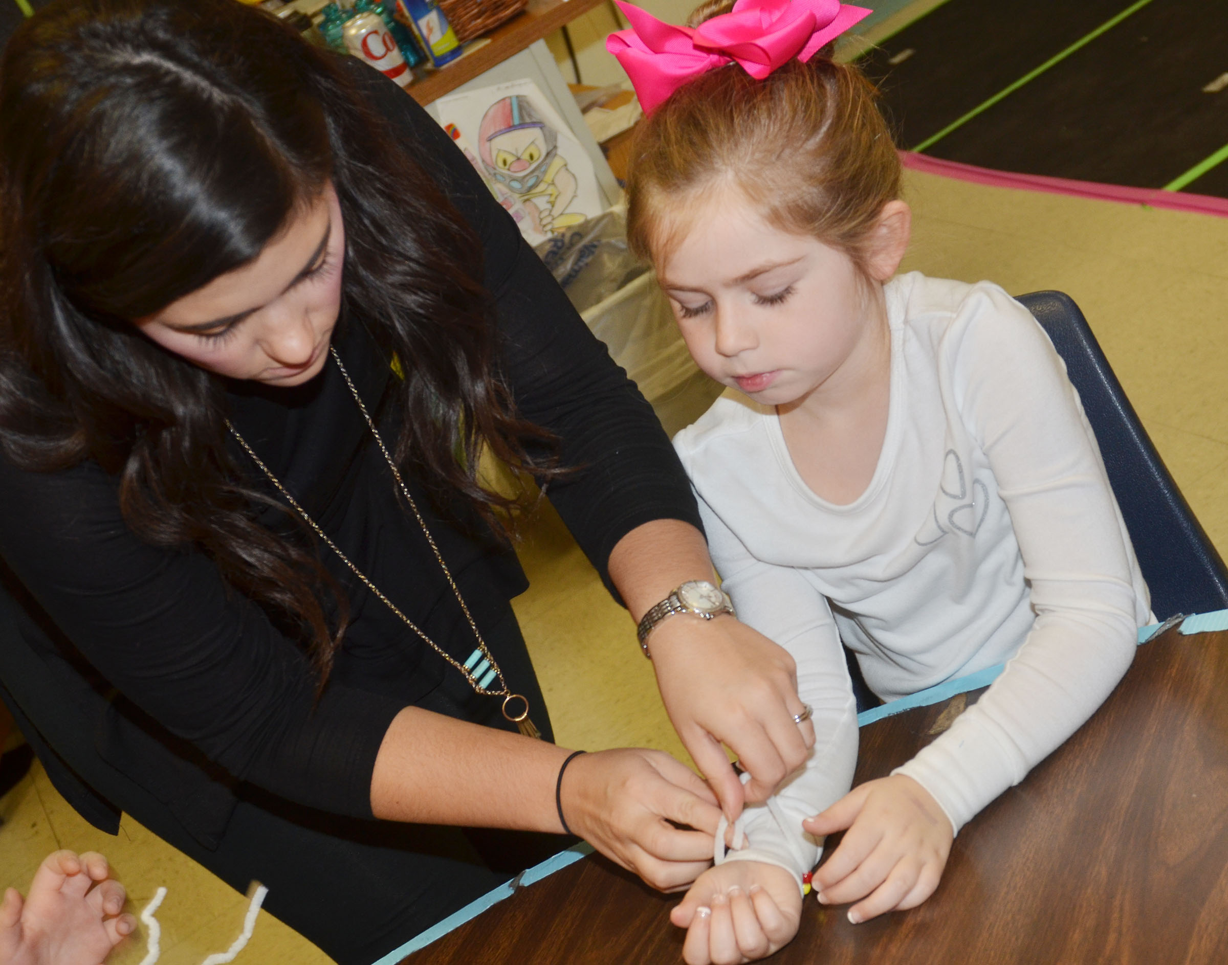 CES teacher Hailey Ogle helps first-grader Lainey Price fasten her Thanksgiving bracelet.