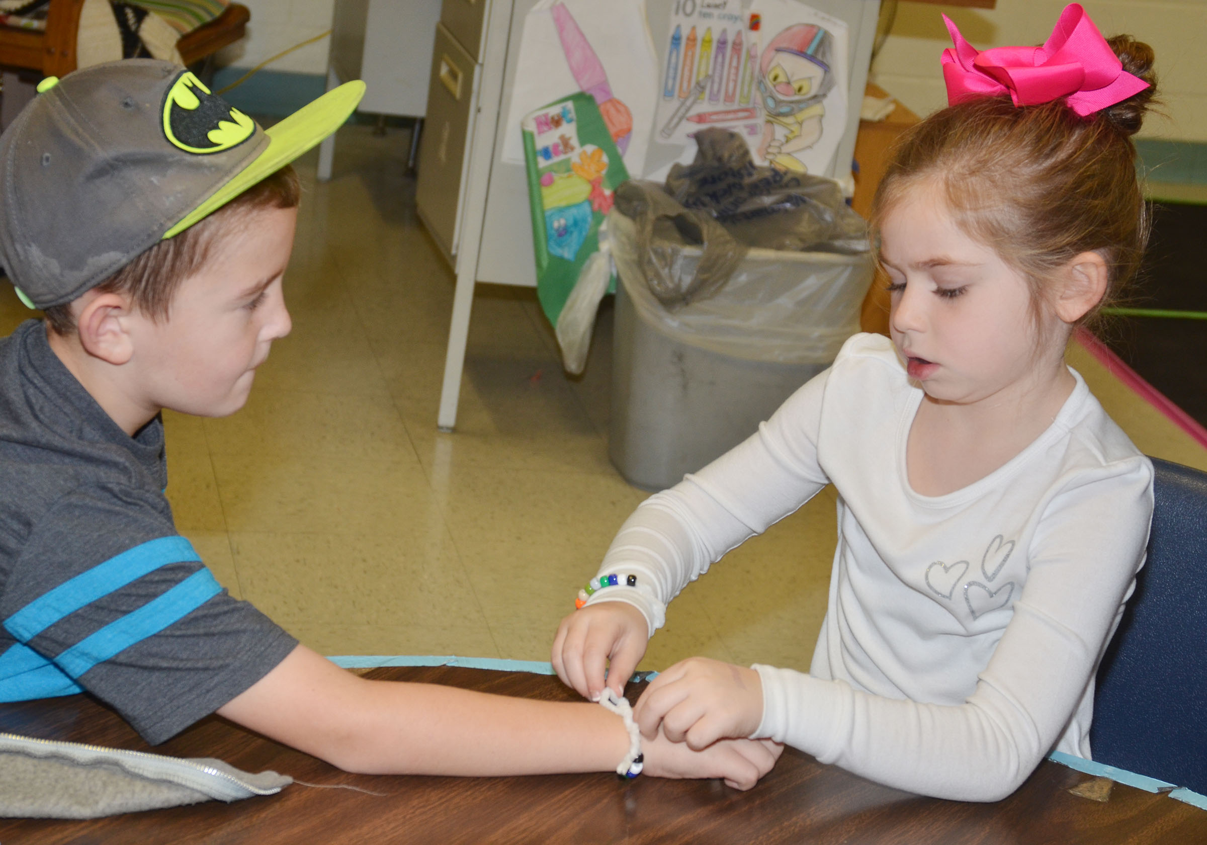 CES first-grader Lainey Price helps classmate Kevin Bradfield fasten his Thanksgiving bracelet.
