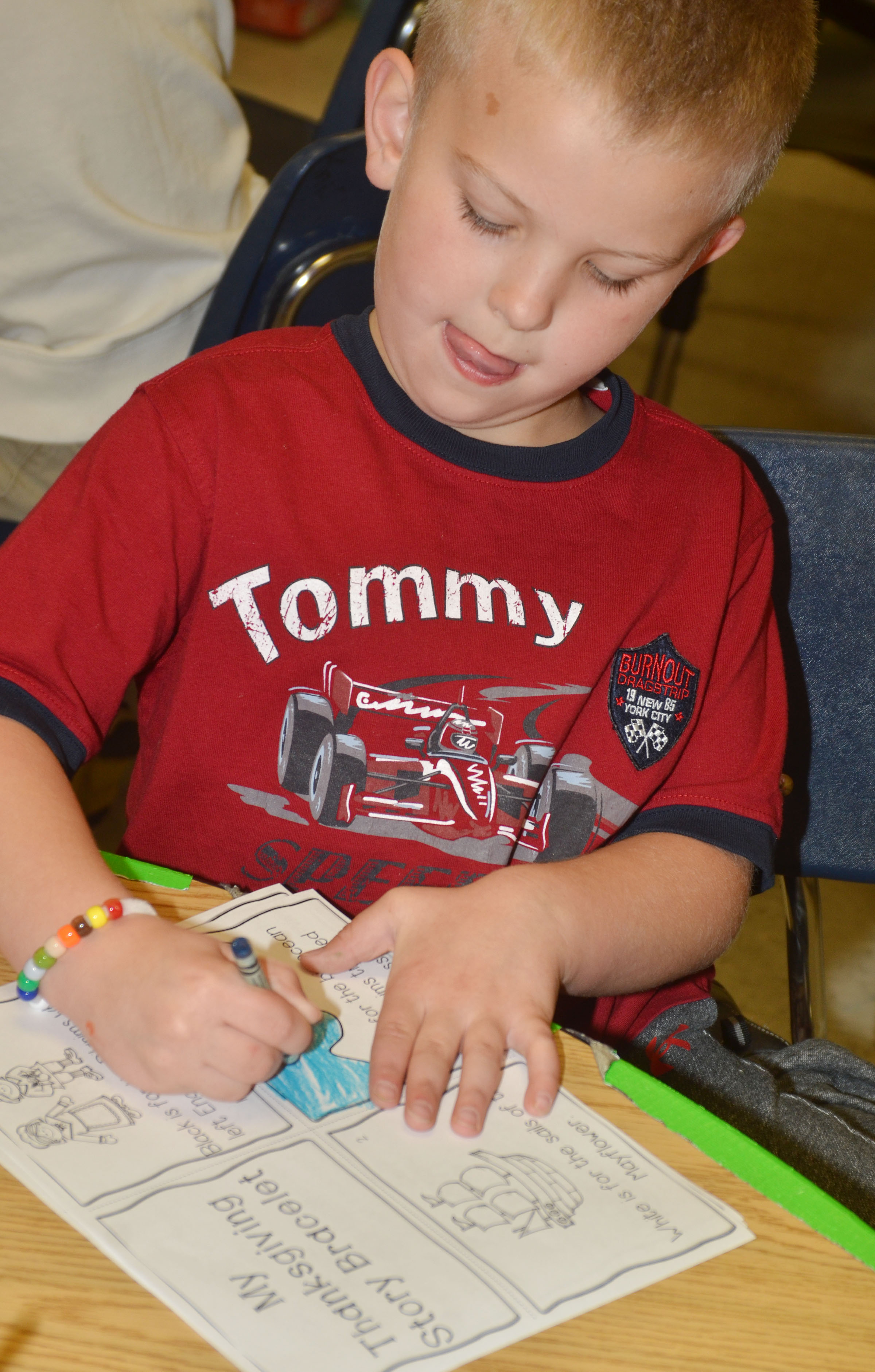 CES first-grader Ethan Bailey colors his Thanksgiving story books.
