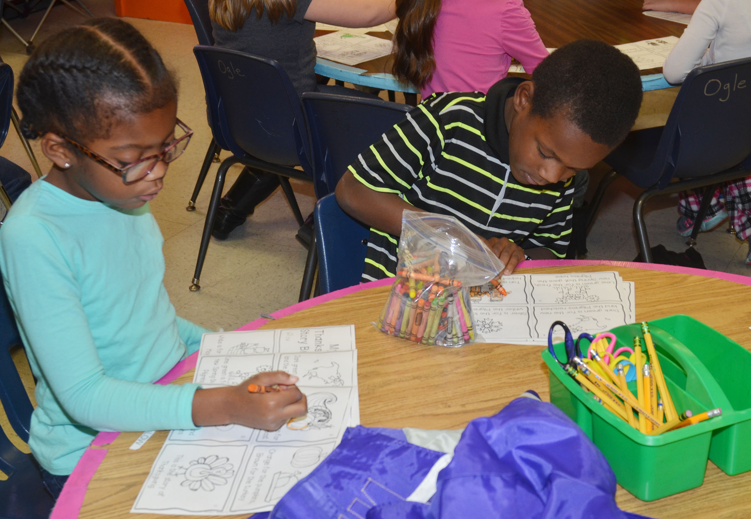 CES first-graders Willow Griffin, at left, and Lazarick Miller color their Thanksgiving story books.