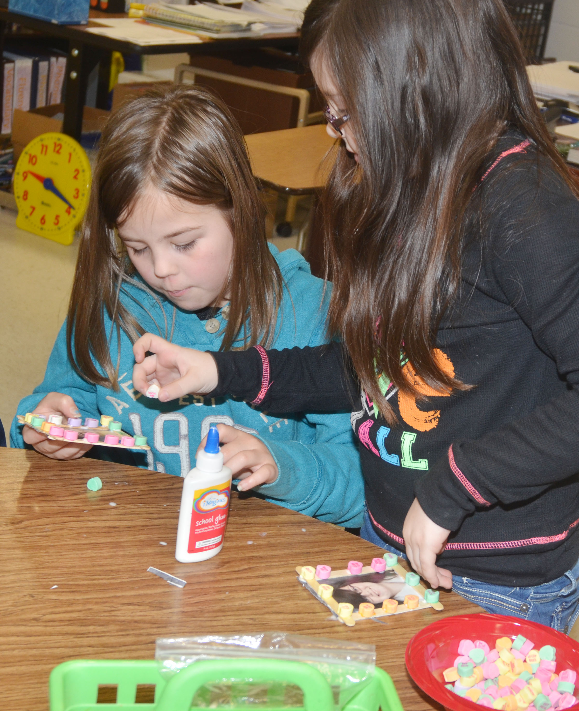 CES third-graders Chloe Bates, at left, and Lauren Pace glue candies on their picture frames.