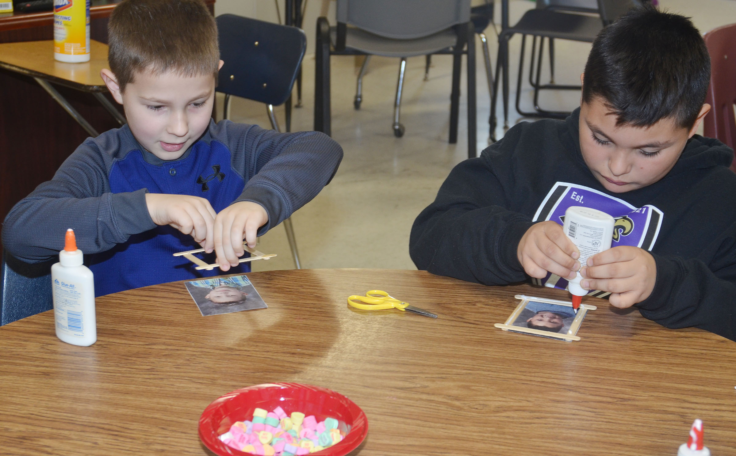 CES third-graders Grayson Dooley, at left, and Brayden Paiz glue their picture frames together.
