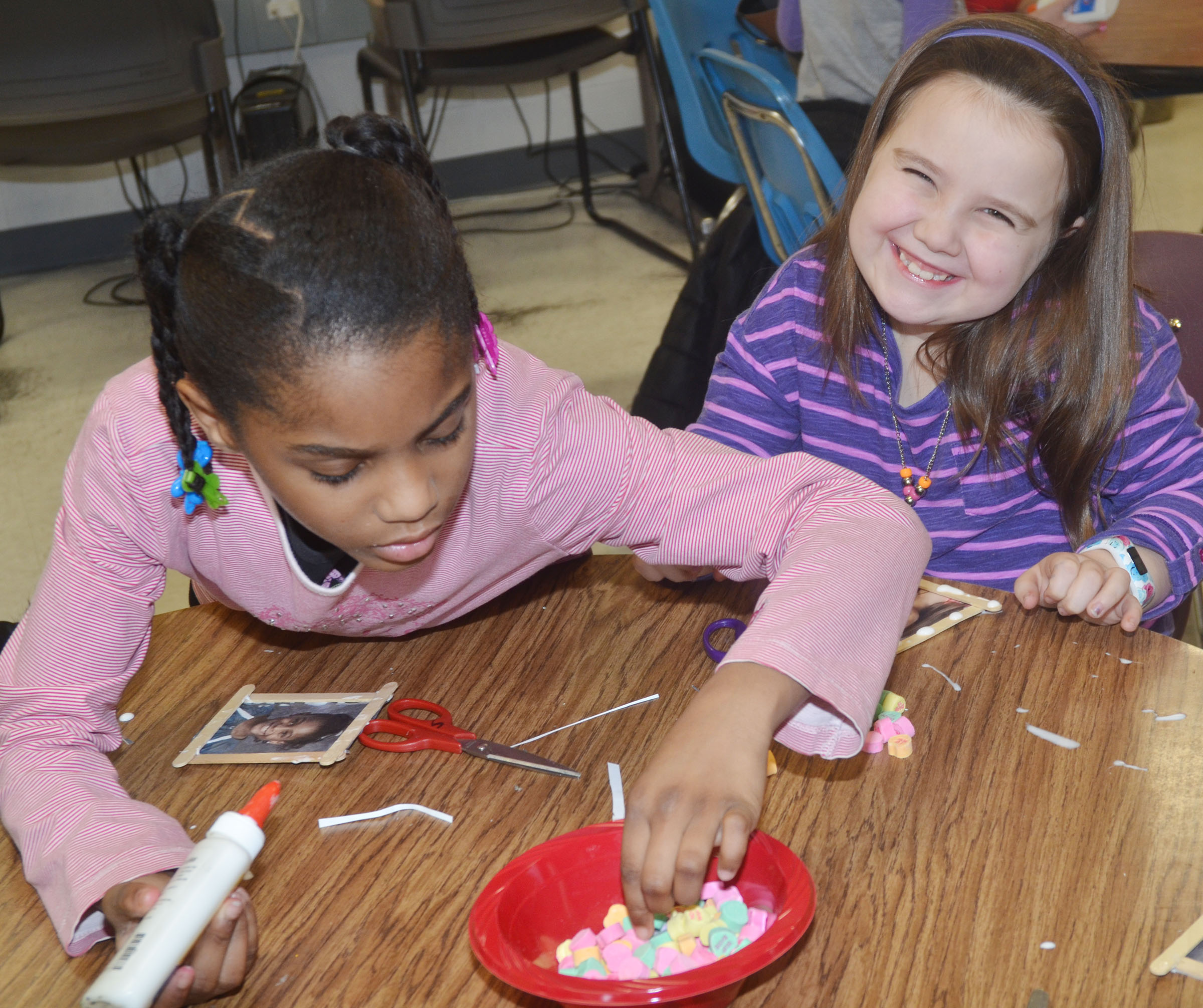 CES third-graders Breona Bridgewater, at left, and Maylee Wilds glue candies on their picture frames.
