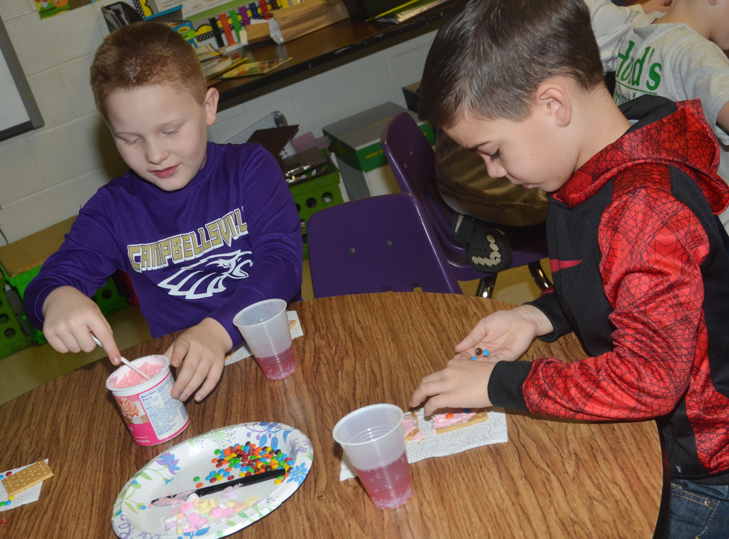 CES third-graders Isaiah Jeffries, at left, and Carson Mills decorate their graham crackers.