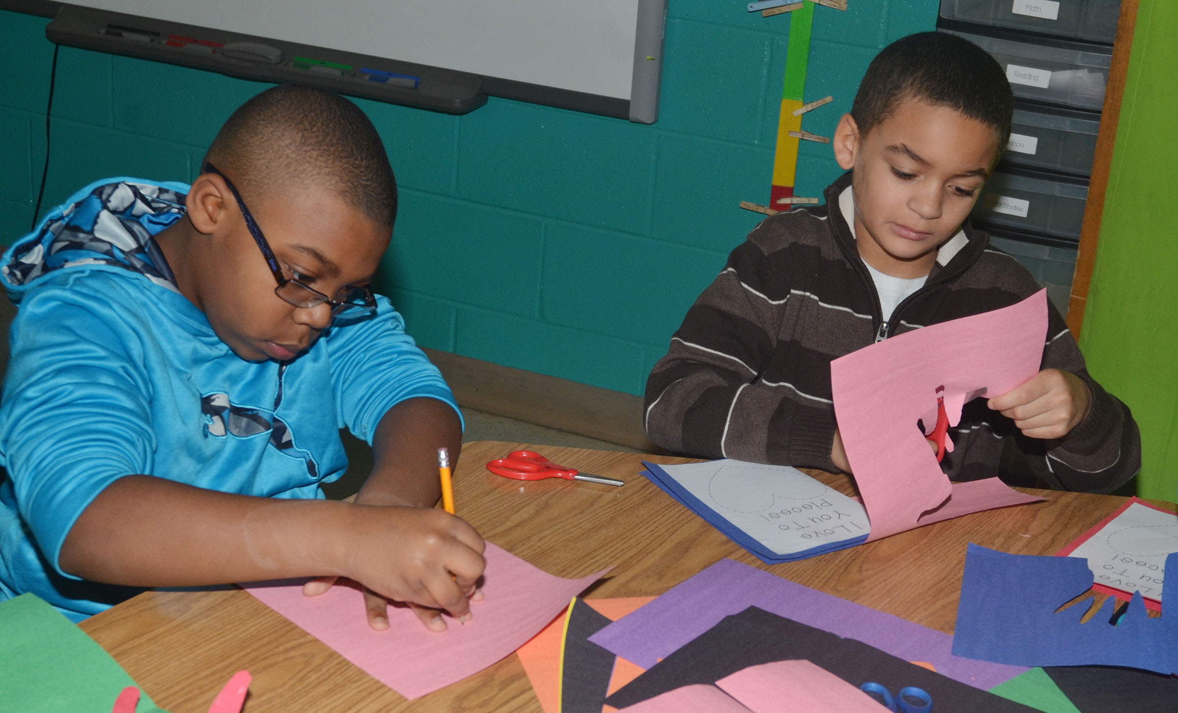 CES third-graders Austin Sloan, at left, and Jaden Barbee make their Valentine cards.