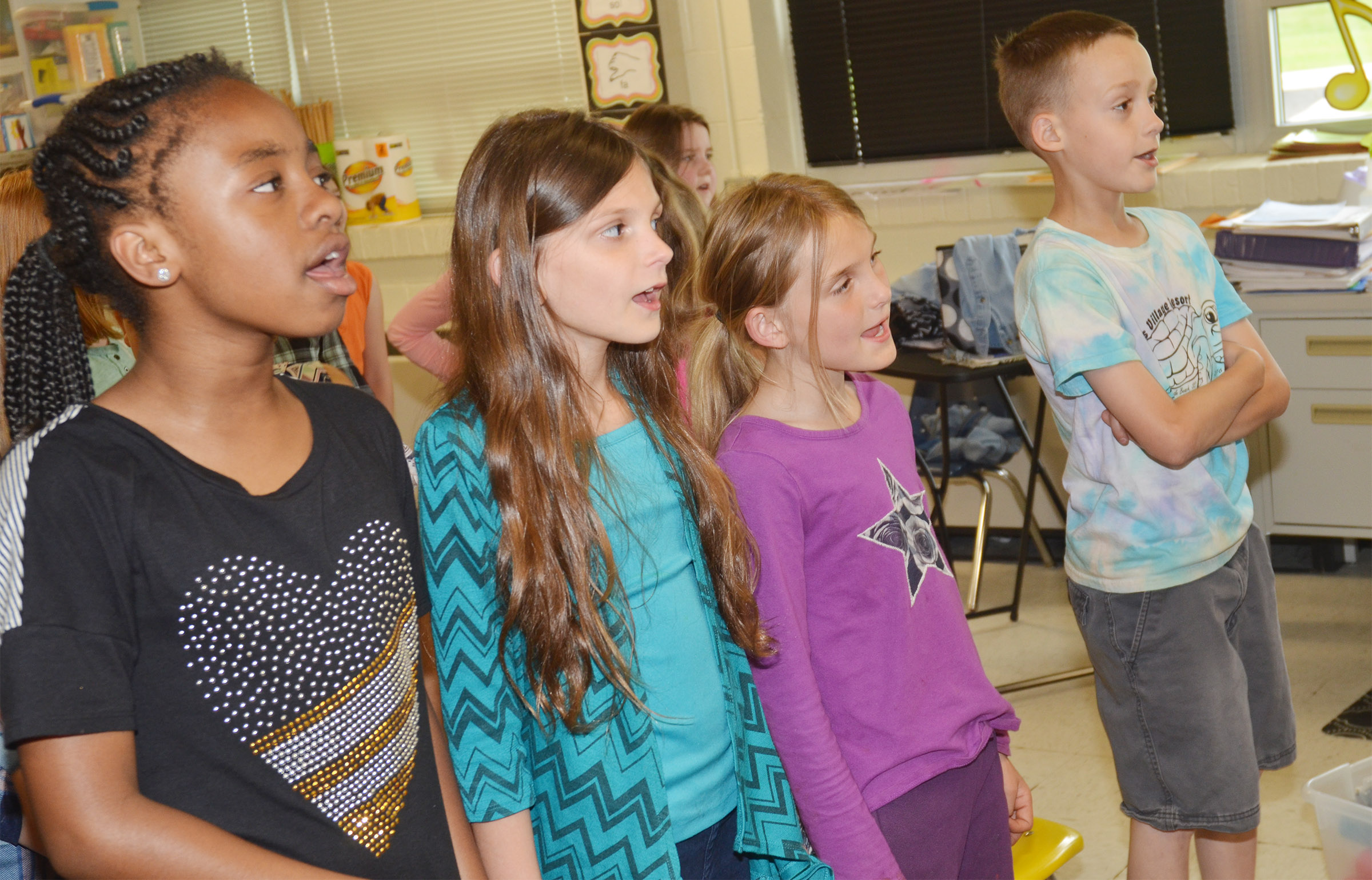 From left, CES third-graders Tiffani Gaddie, Madie Gebler, Miranda Edwards and Caysen Tungate sing with the third-grade choir.