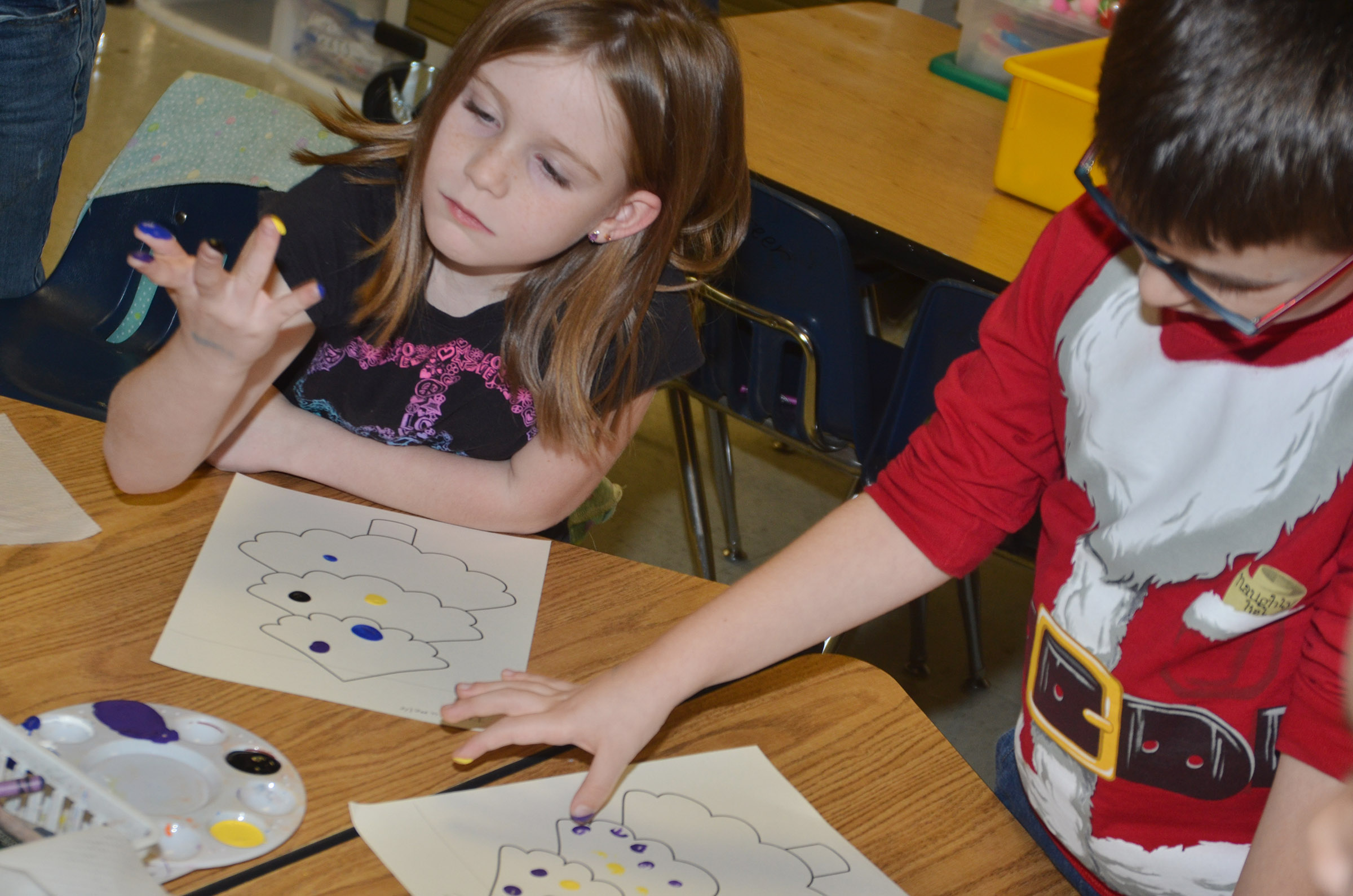 CES first-graders Isabella Brunelle, at left, and Sawyer Lange paint their Christmas trees.