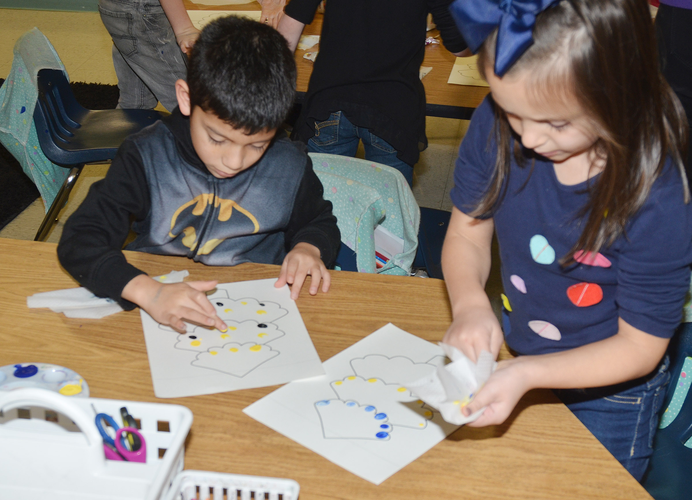 CES first-graders Trey Guajardo, at left, and Serenity Taylor paint their Christmas trees.