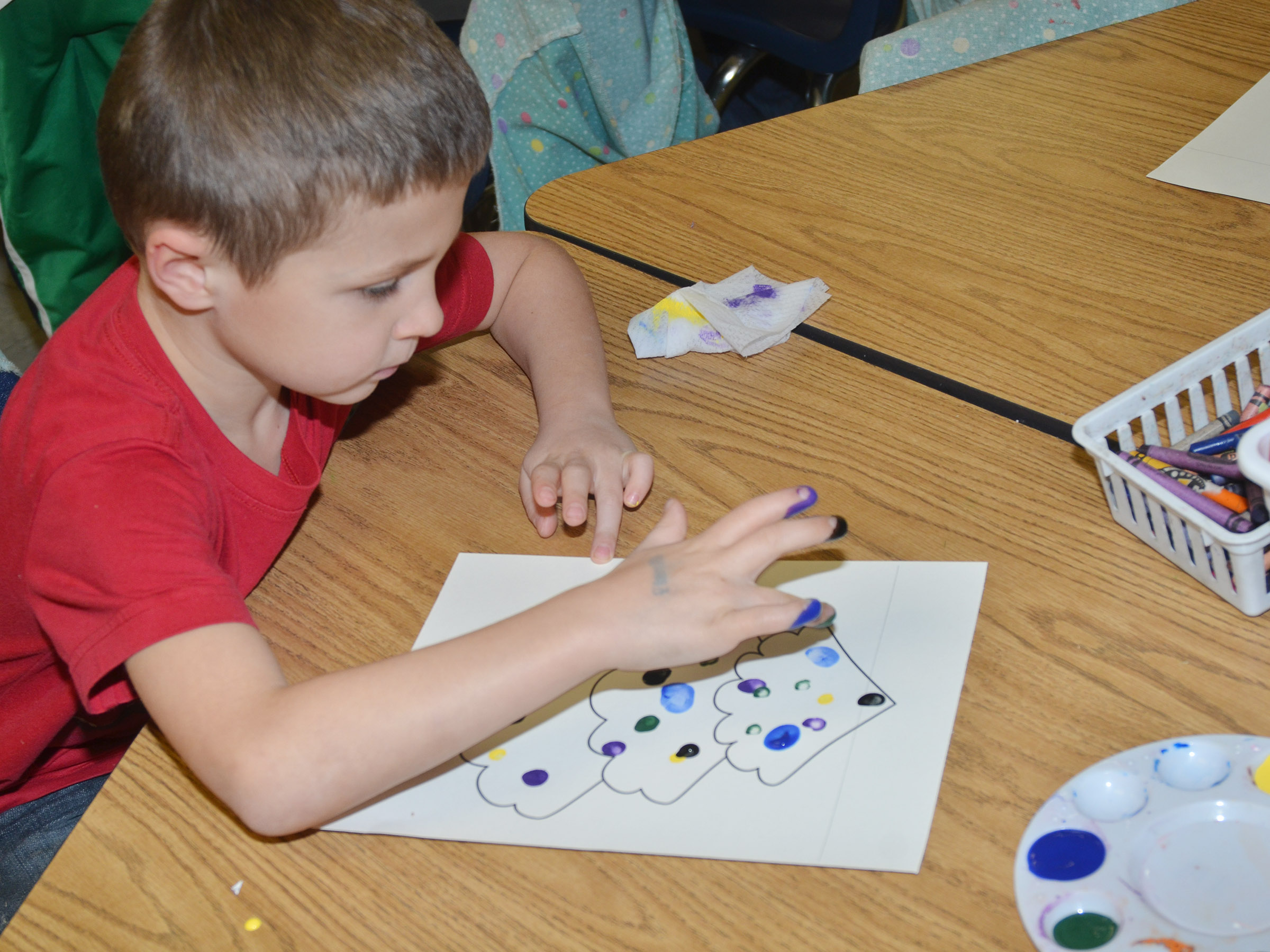 CES first-grader Bryson Gabehart paints his Christmas tree.