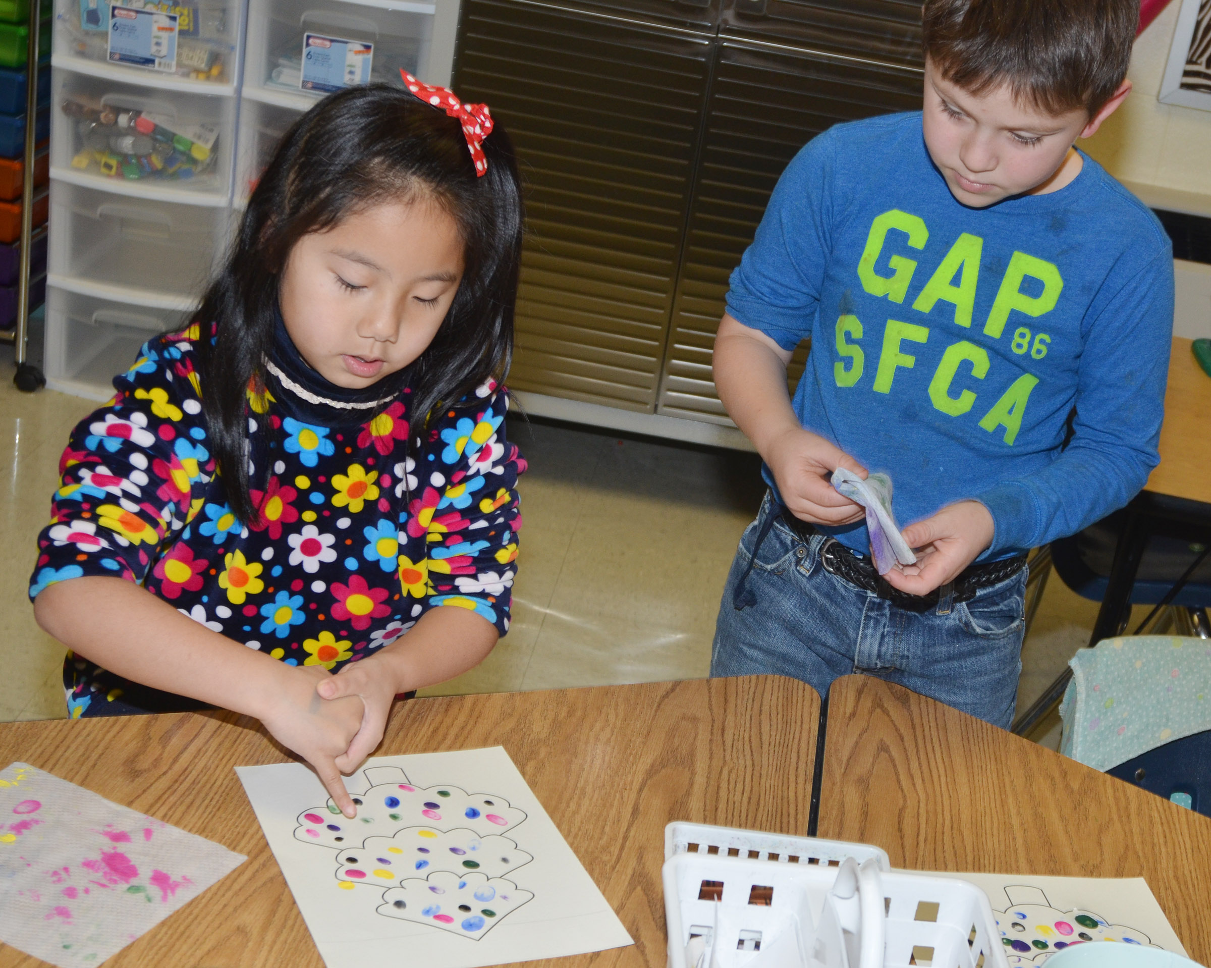 CES first-graders Tina Yiang, at left, and Fabrizio Segura paint their Christmas trees.