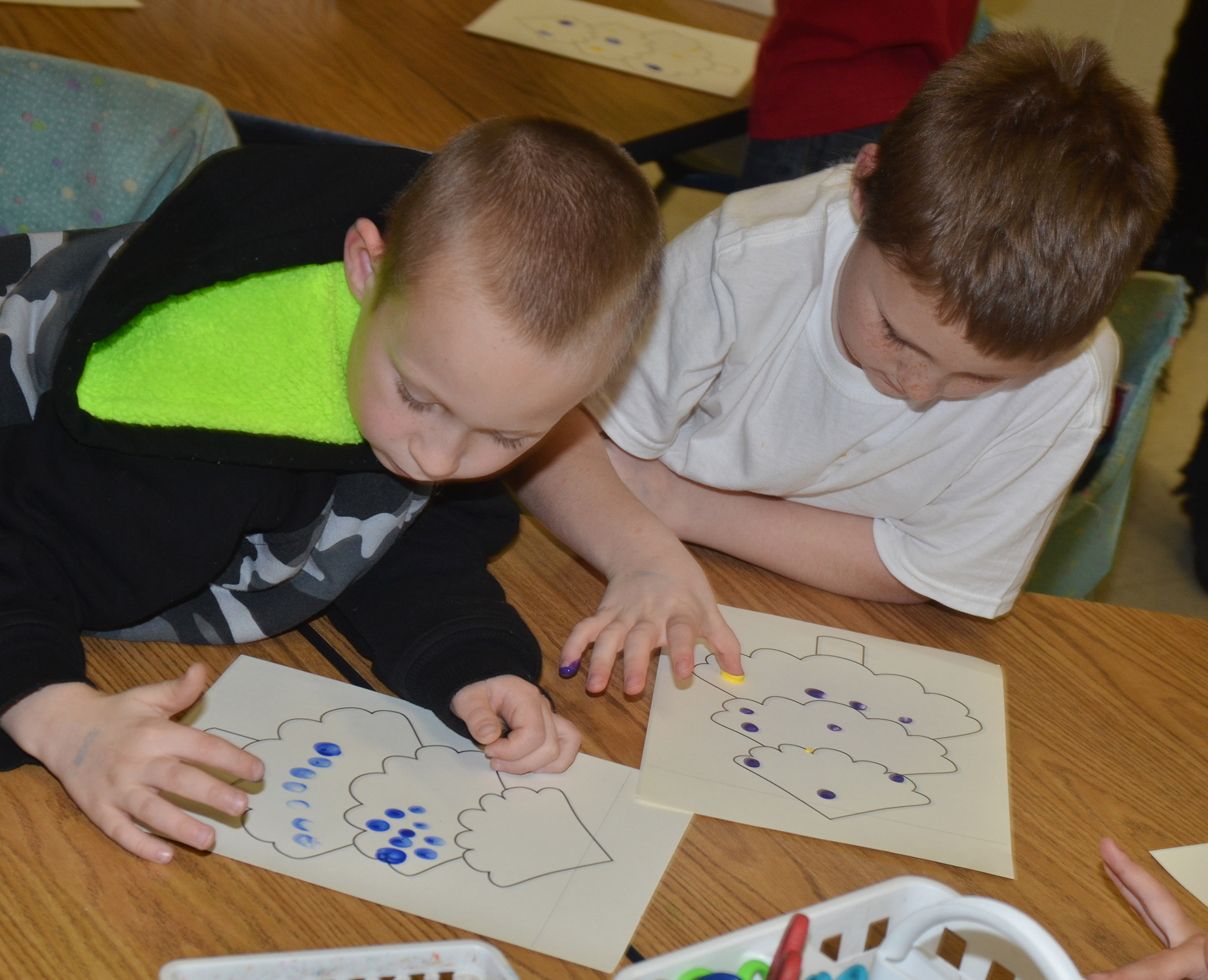CES first-graders Raleigh Spencer, at left, and James Brunner paint their Christmas trees.