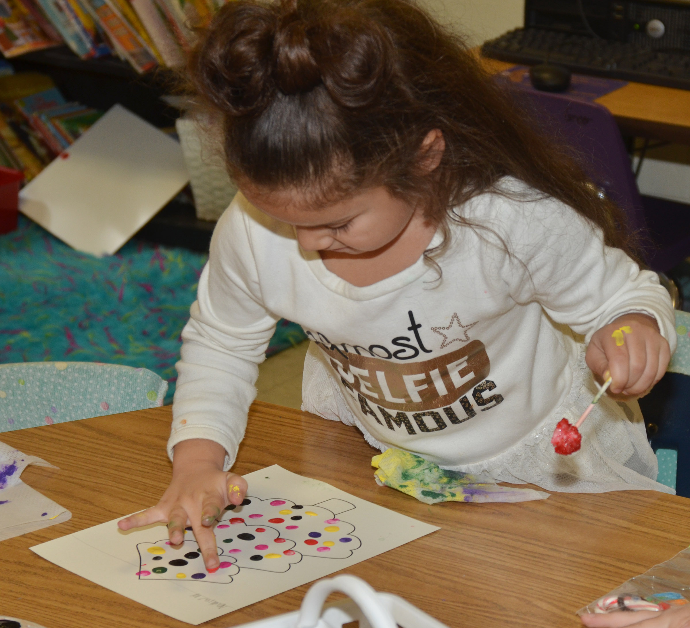 CES first-grader Nadia Taylor paints her Christmas tree.