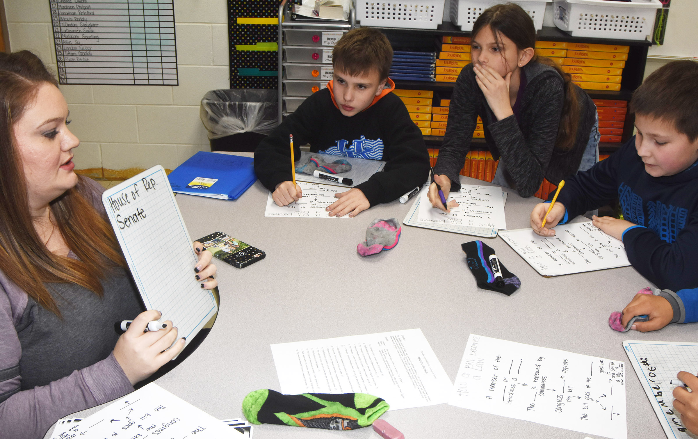 CES teacher Ann-Michael Tucker talks to students, from left, fifth-graders Jayden Harris, Madie Gebler and Grayson Dooley about how a bill becomes a law.