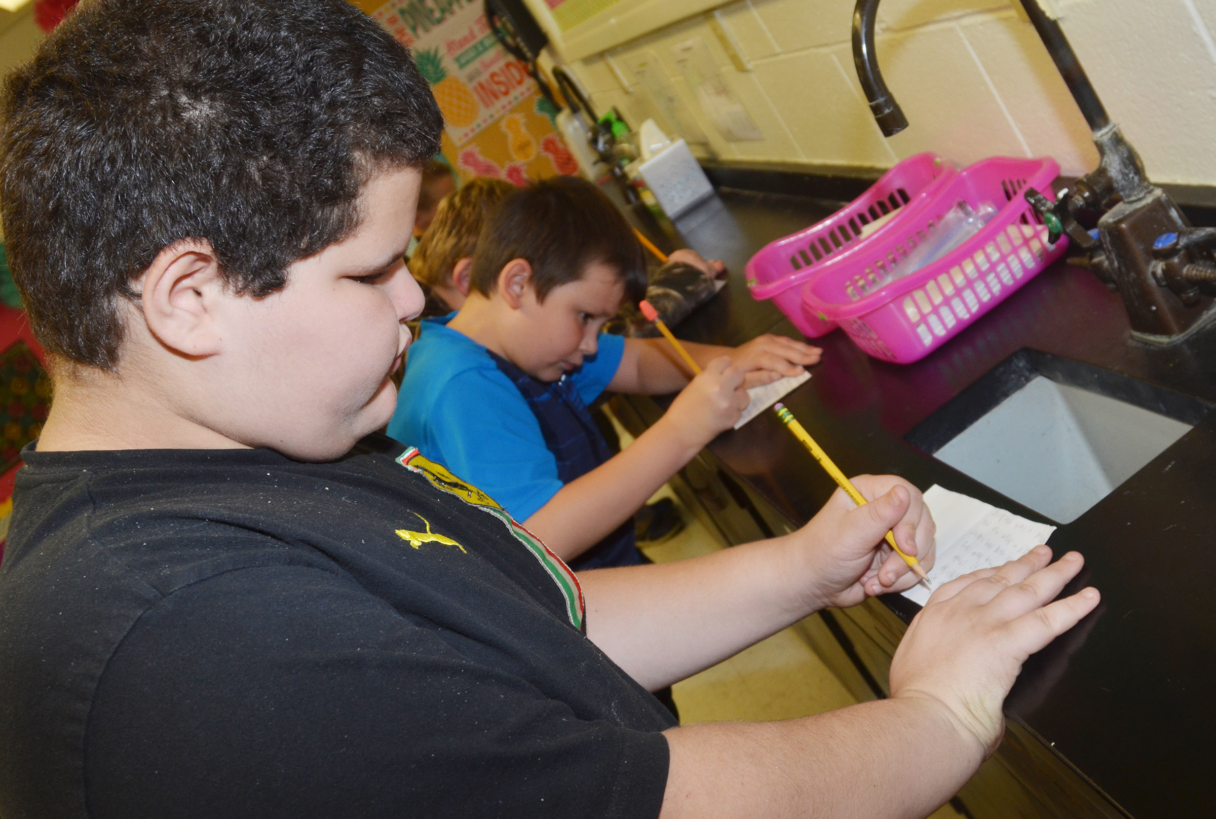 CES fifth-grader Steven Miller writes a supporting detail in his mini-book.