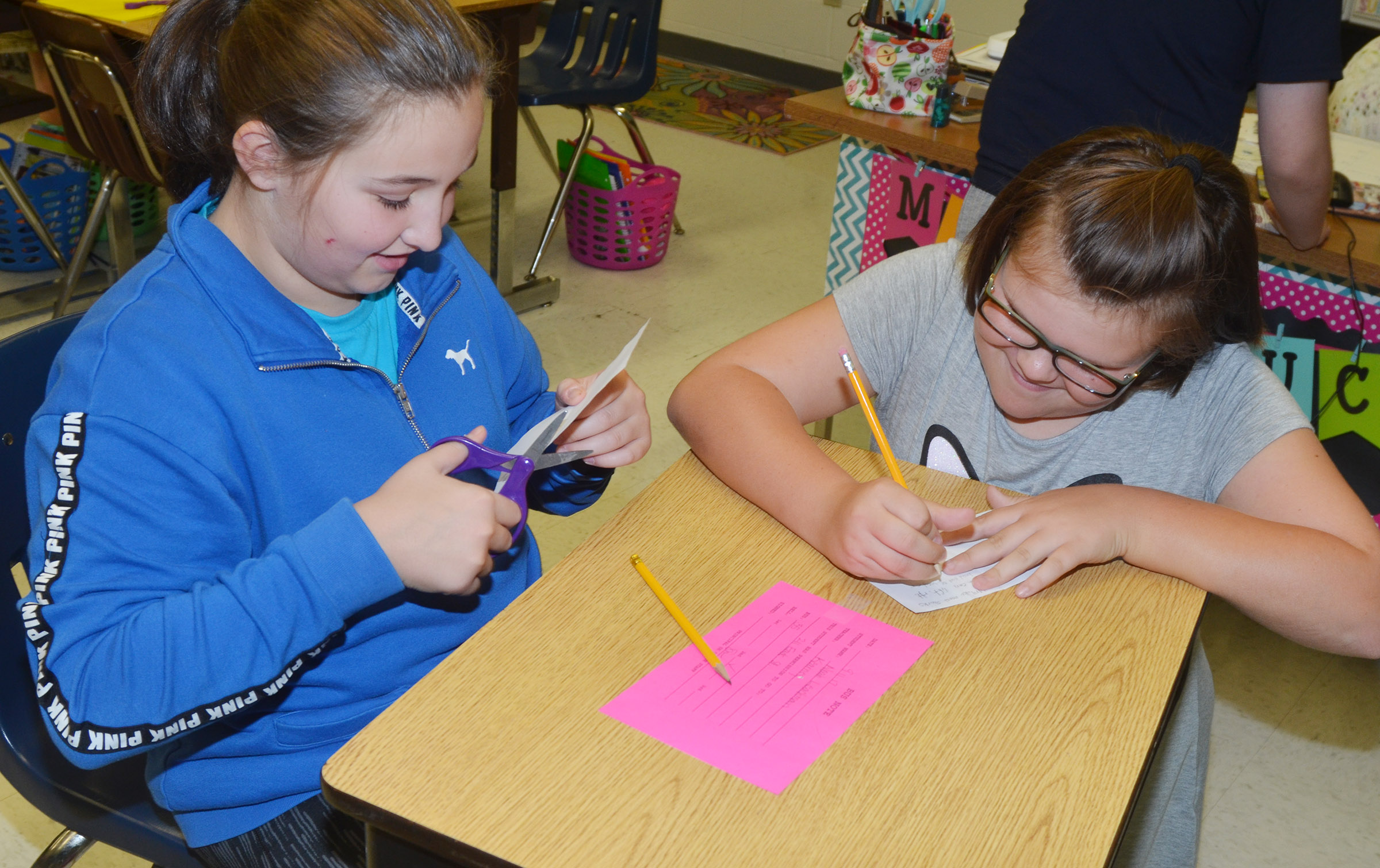CES fifth-graders Riley Newton, at left, and Keeley Dicken work on their mini-books.